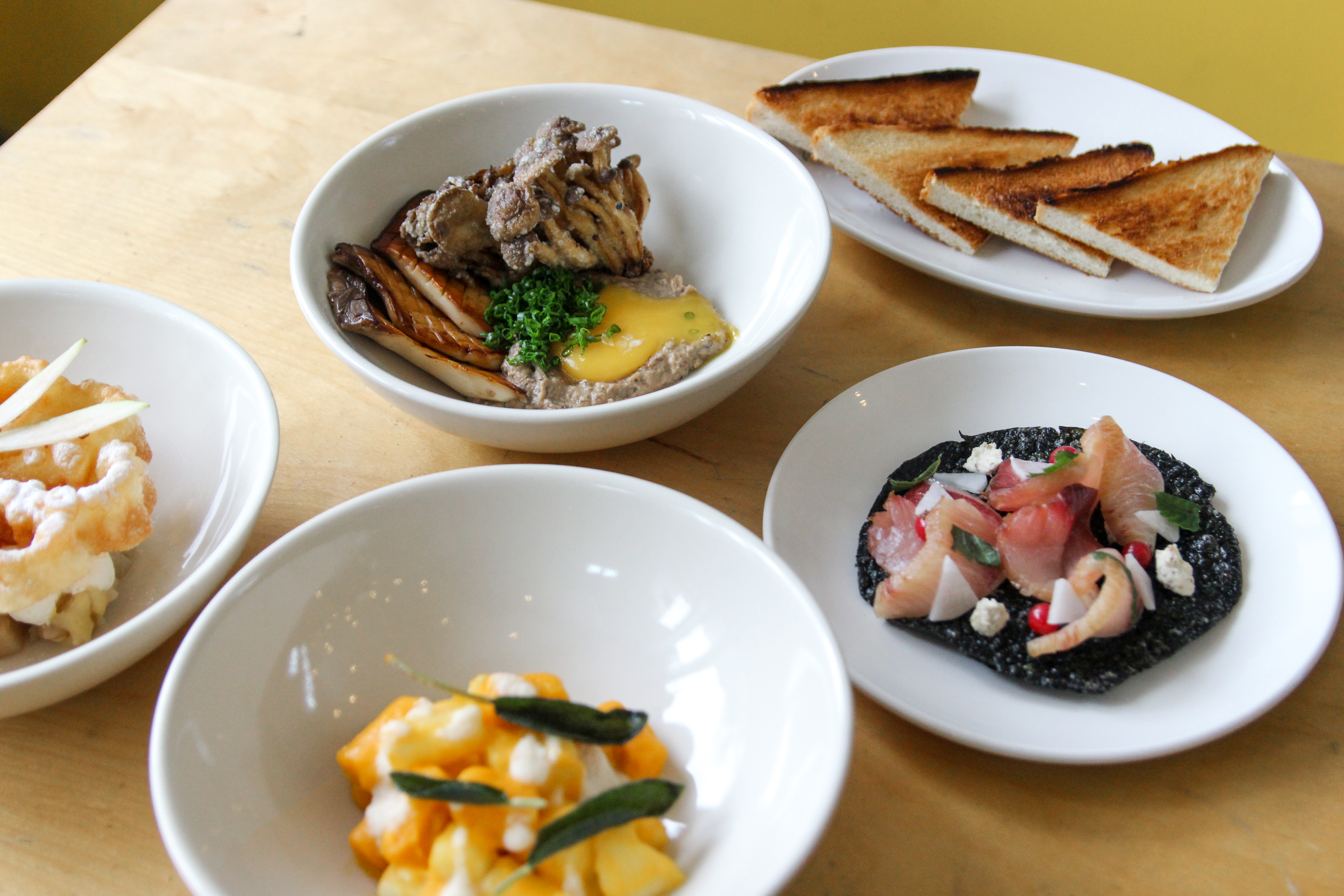 Several dishes composed of stylishly plated foods sitting on a wooden table