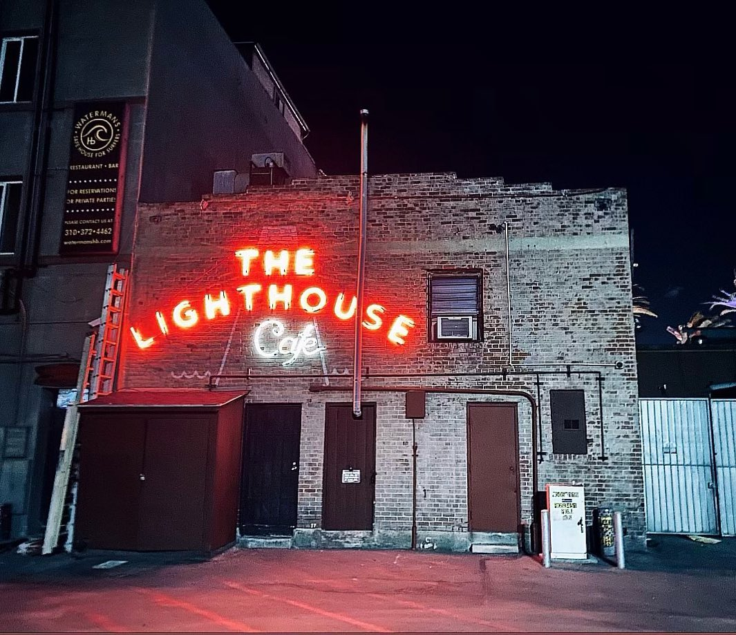 A brick exterior of a neon-lit bar at night.