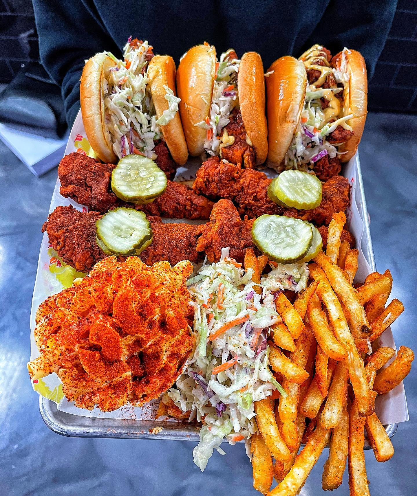 Fried chicken sliders, tenders with pickles on top, angry mac and cheese, coleslaw, and fries in a box.