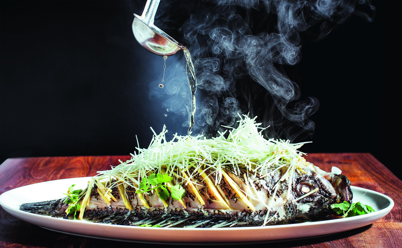 A fish dish with smoke wafting upward