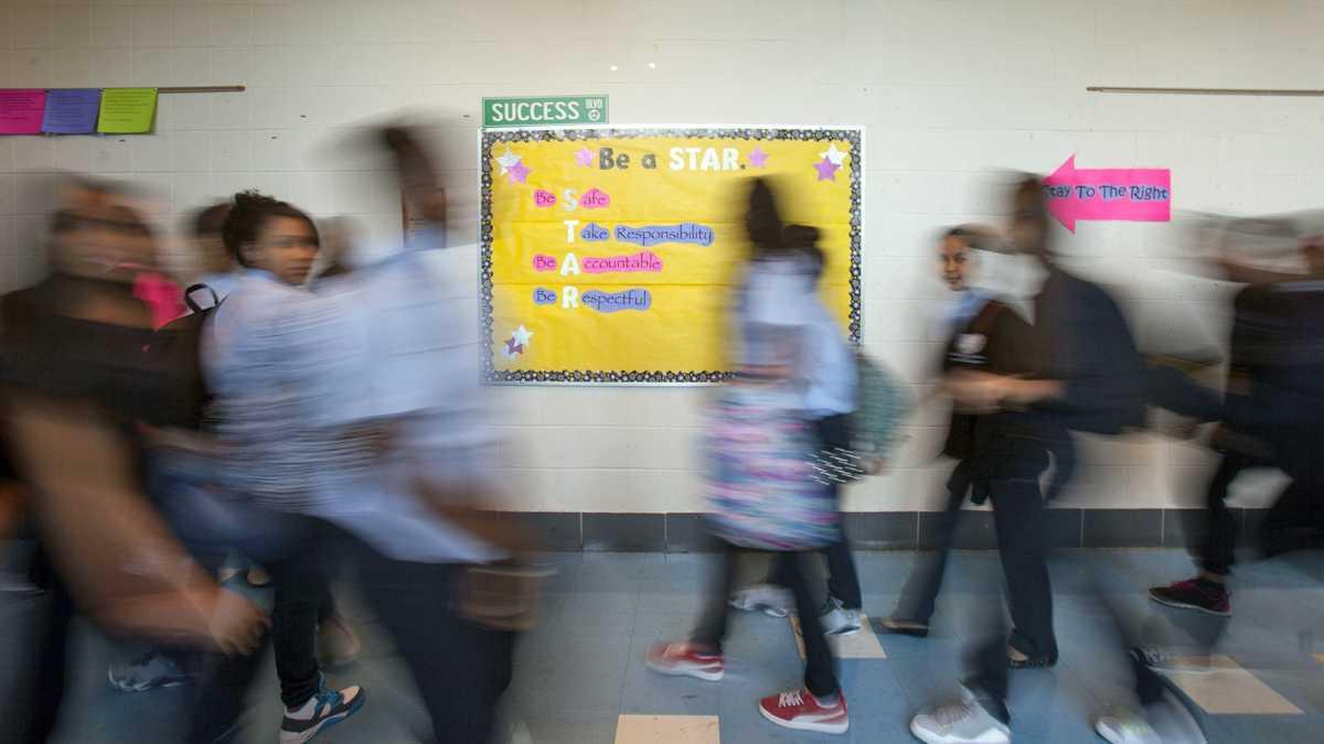 Long exposure shot of students walking through a hallway.