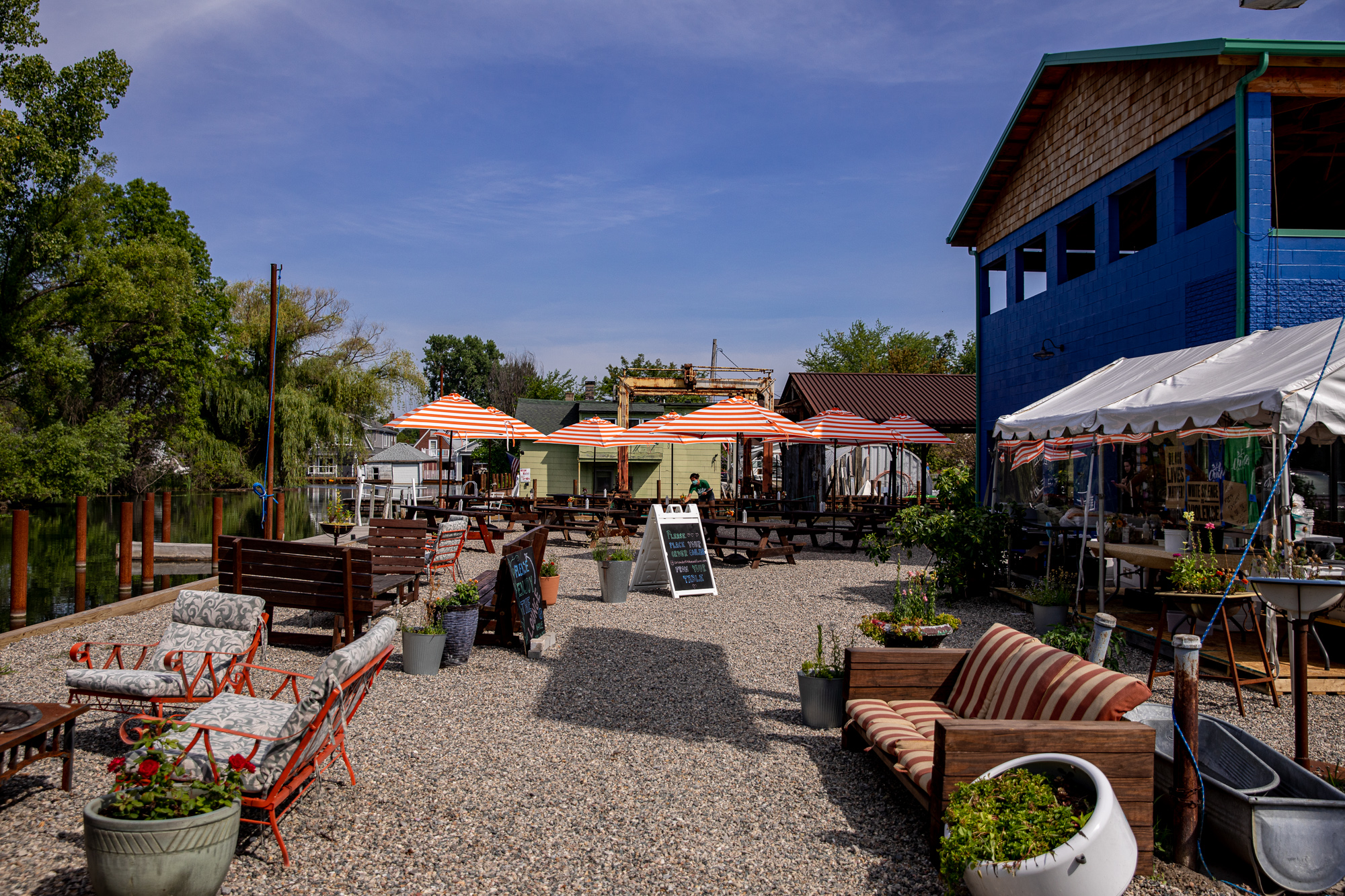 A blue building next to patio chairs, a fire pit, a couch, a tent with Coriander's prep kitchen, and picnic tables with umbrellas in the distance.