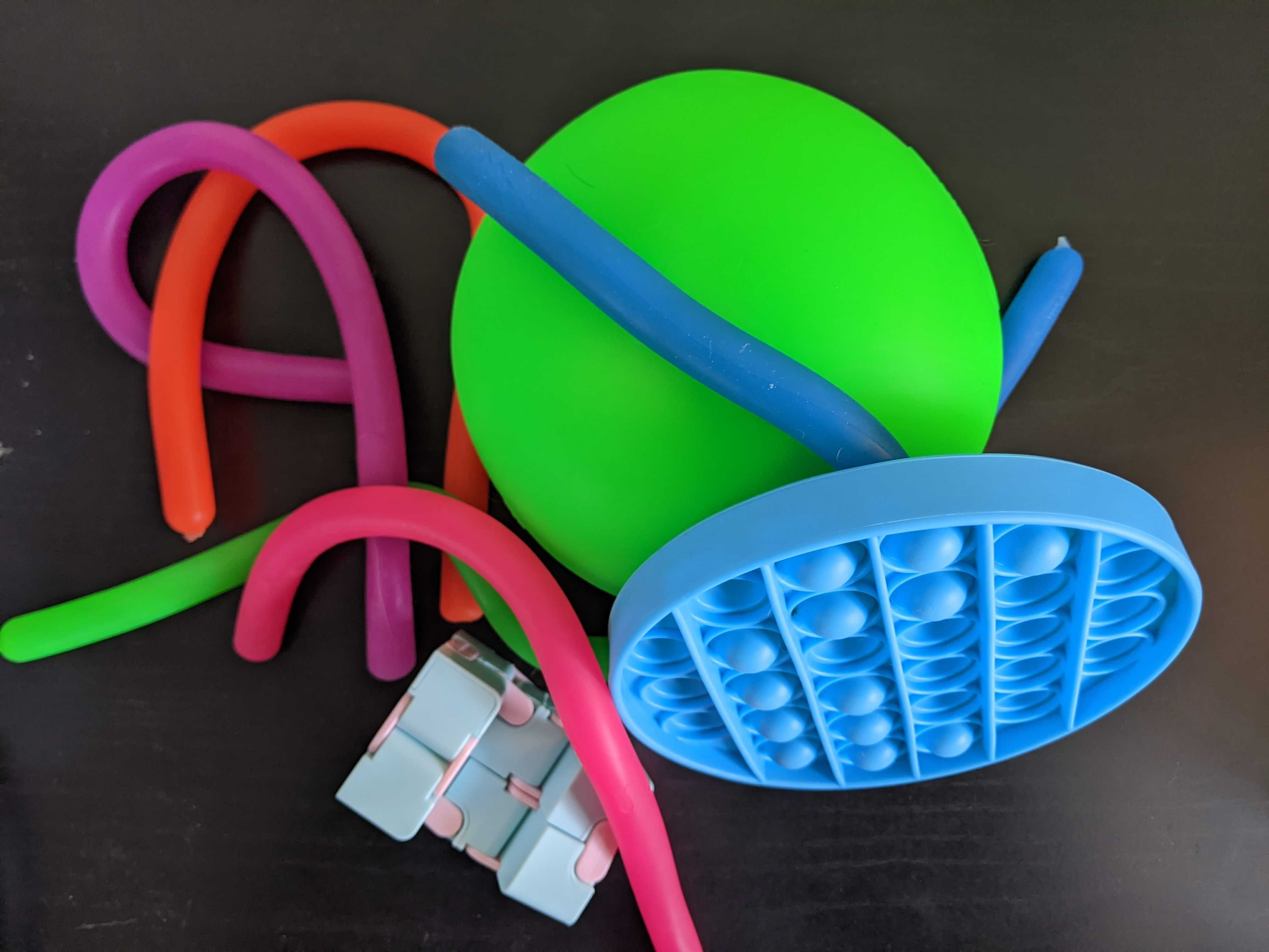 A pile of bright, neon colored fidget toys. Some are long rubber noodles, there's a giant neon green stress ball, a push pop bubble, and an infinity cube.