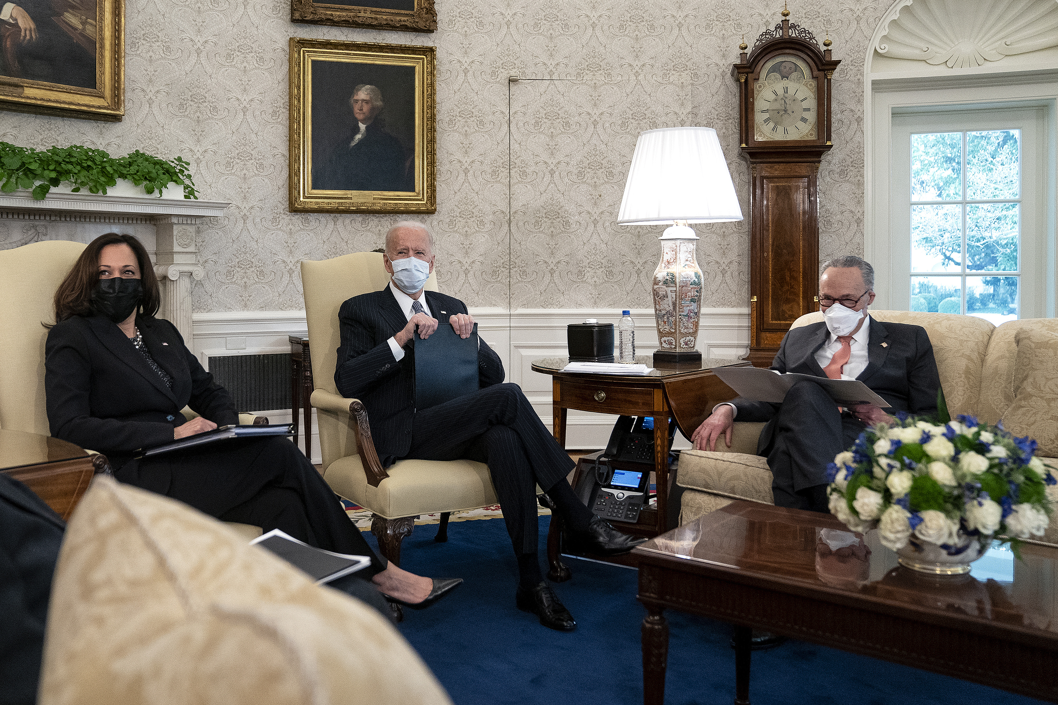 Harris, Biden, and Schumer, all wearing masks and dark suits, sit in an ornately furnished room, talking, with documents in front of them.