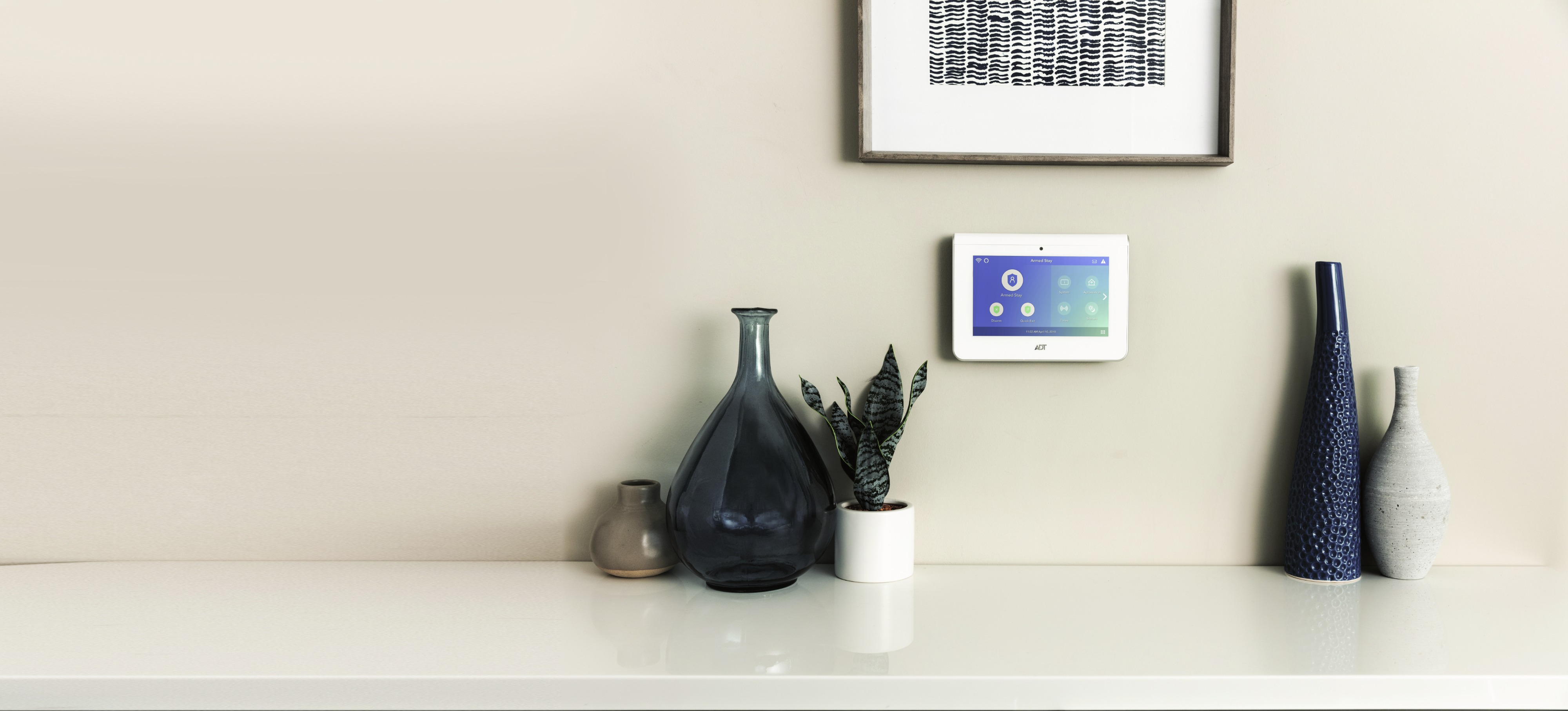 An ADT security system on the wall of a home with a vase, plant, and framed decorative print surrounding it.