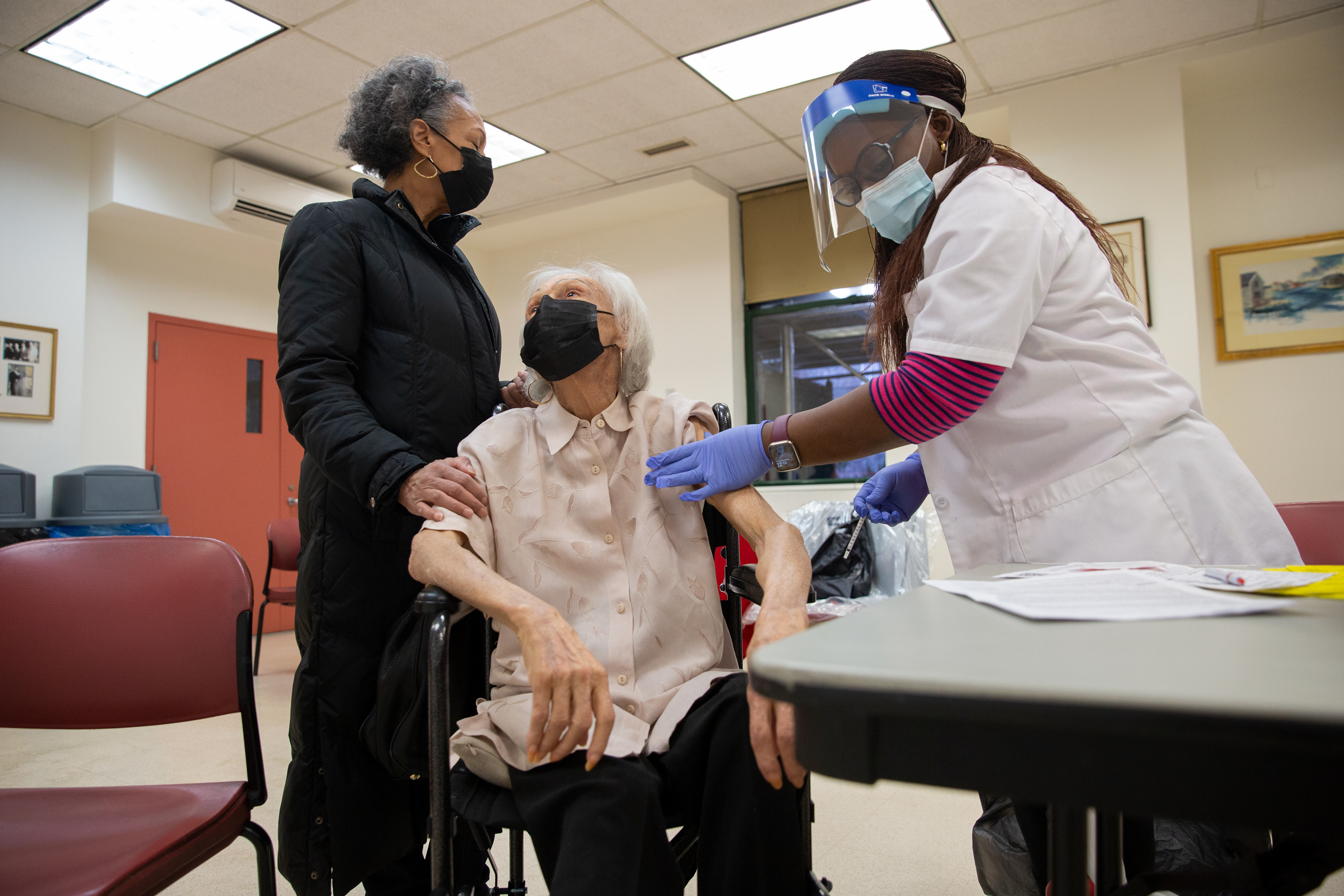 Maritza Cadrera helps comfort her 93-year-old mother, Antonia Villanueva, while the Wien House resident receives her second coronavirus vaccine, March 3, 2021.
