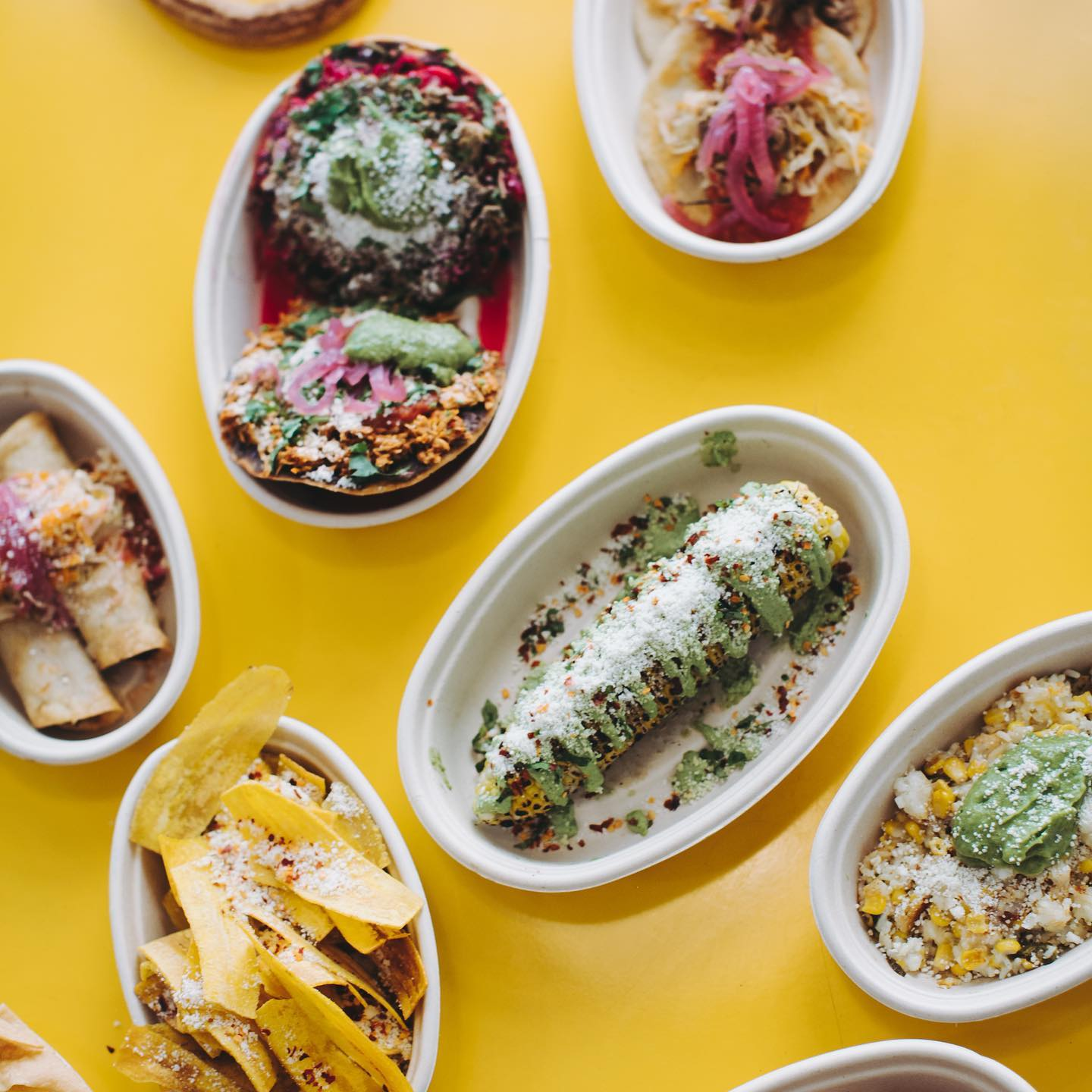 a yellow background with taquitos, plantain chips, and other Guatemalan and Salvadorian street food from El Merkury