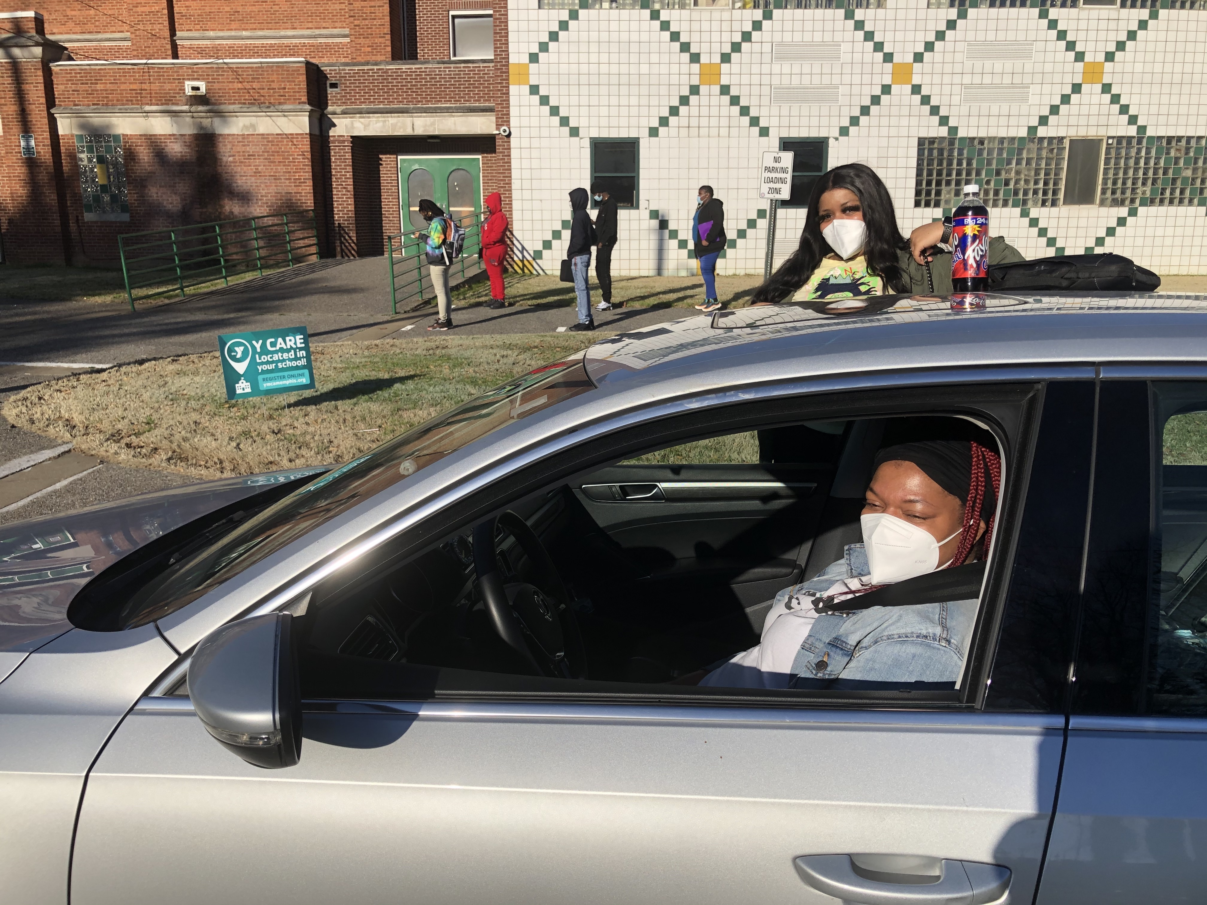 A masked parent in the driver's seat of a car and her masked daughter exiting the car in front of the school, as students stand apart in line to enter the building.