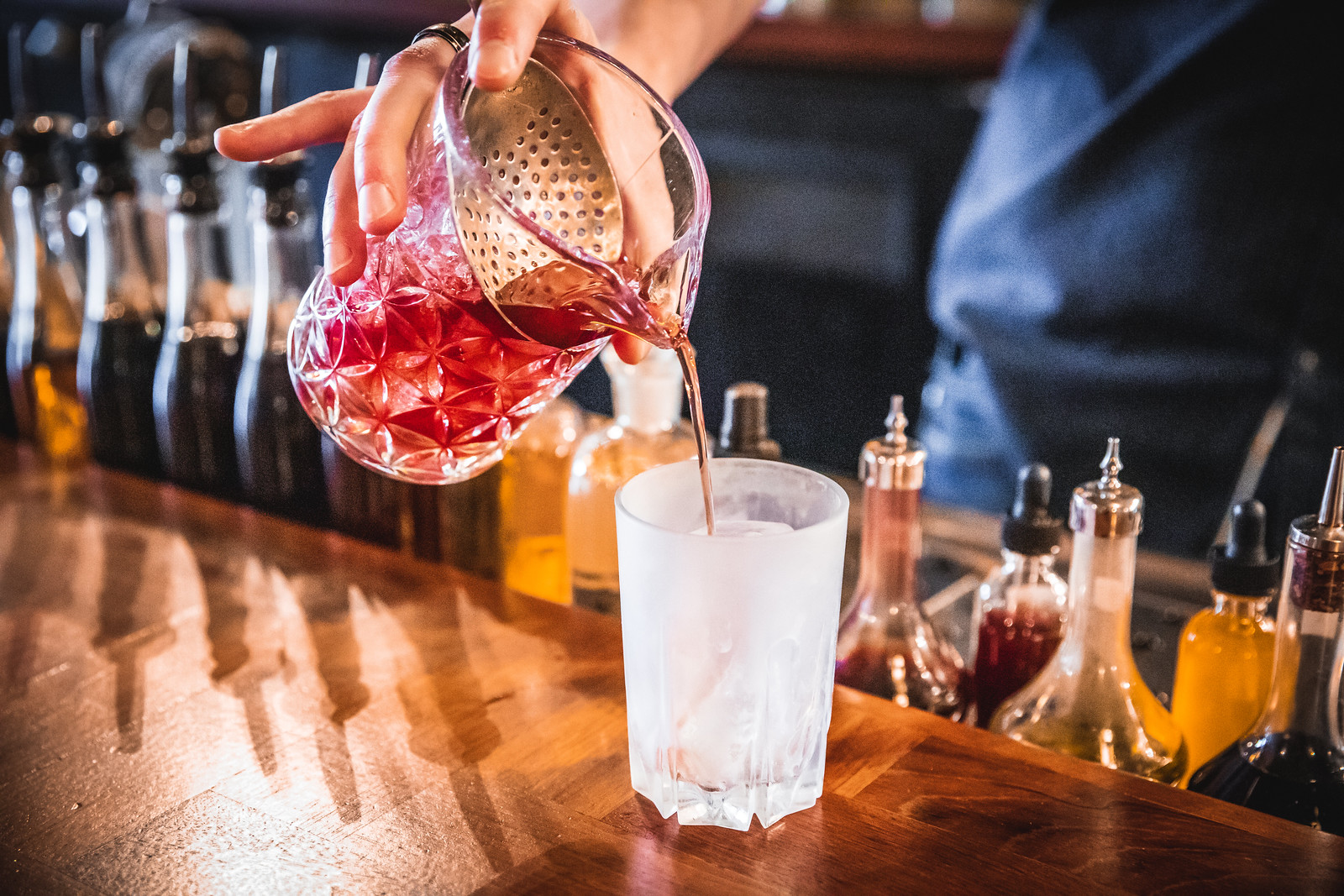 A red drink getting poured into a frosty glass.