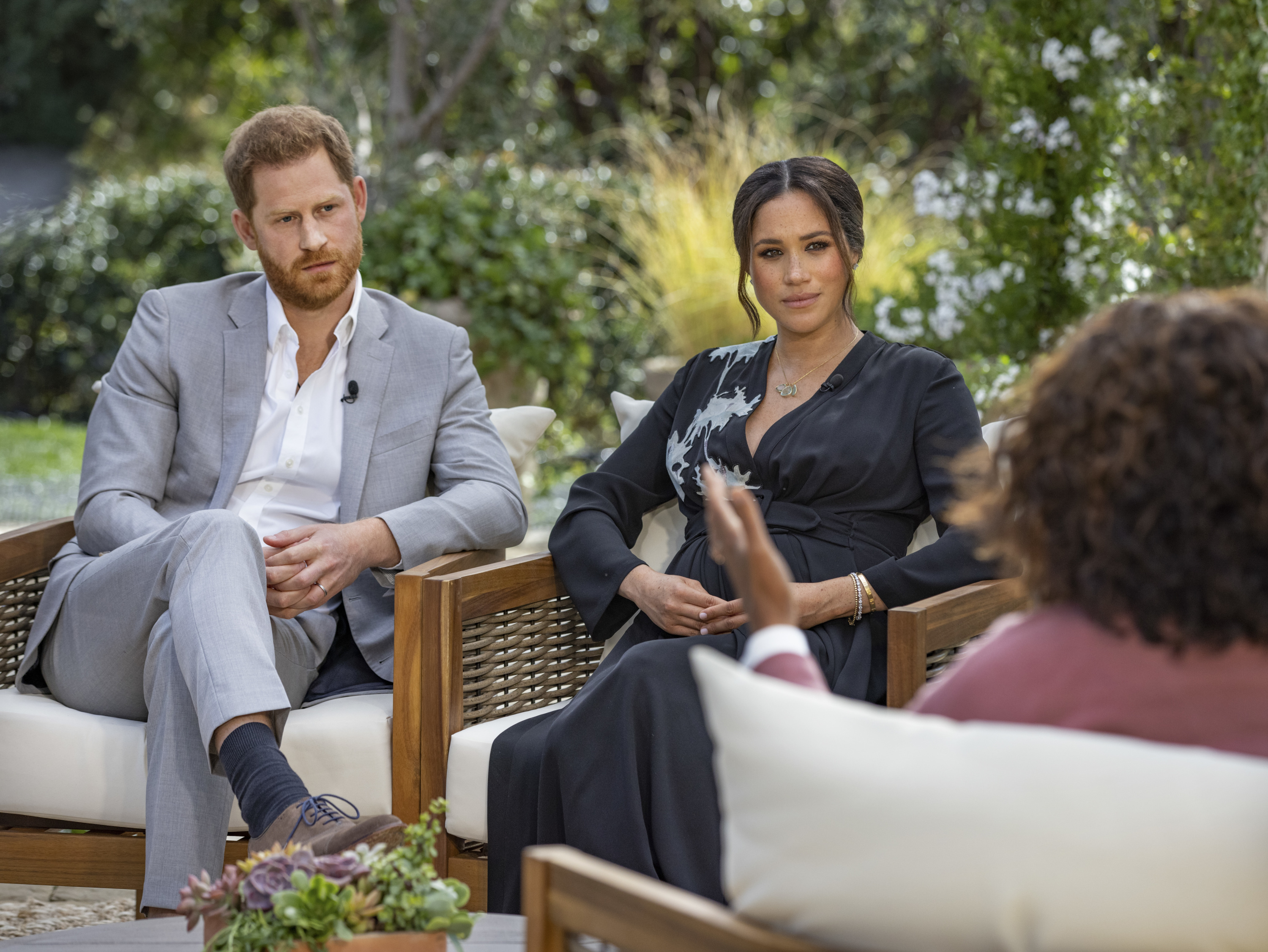 Prince Harry and Meghan Markle sit in chairs opposite Oprah