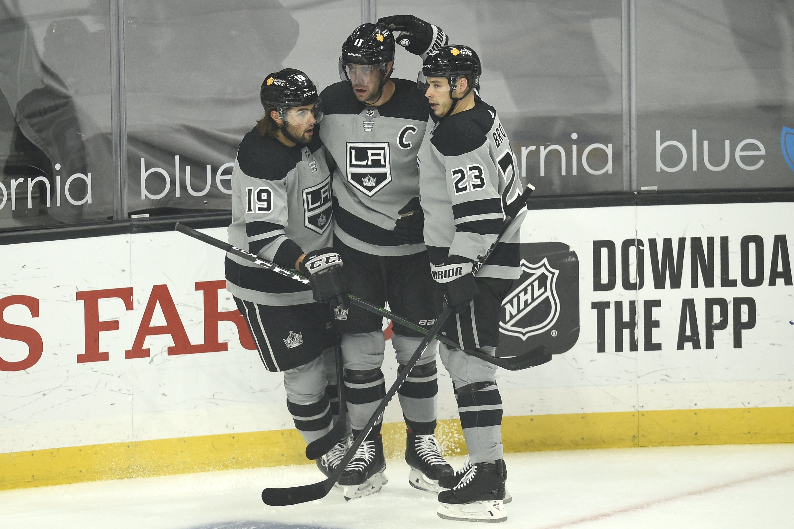 Los Angeles Kings center Anze Kopitar (center) celebrates his goal with right wing Dustin Brown (23) and right wing Alex Iafallo (19) during the first period at Staples Center.