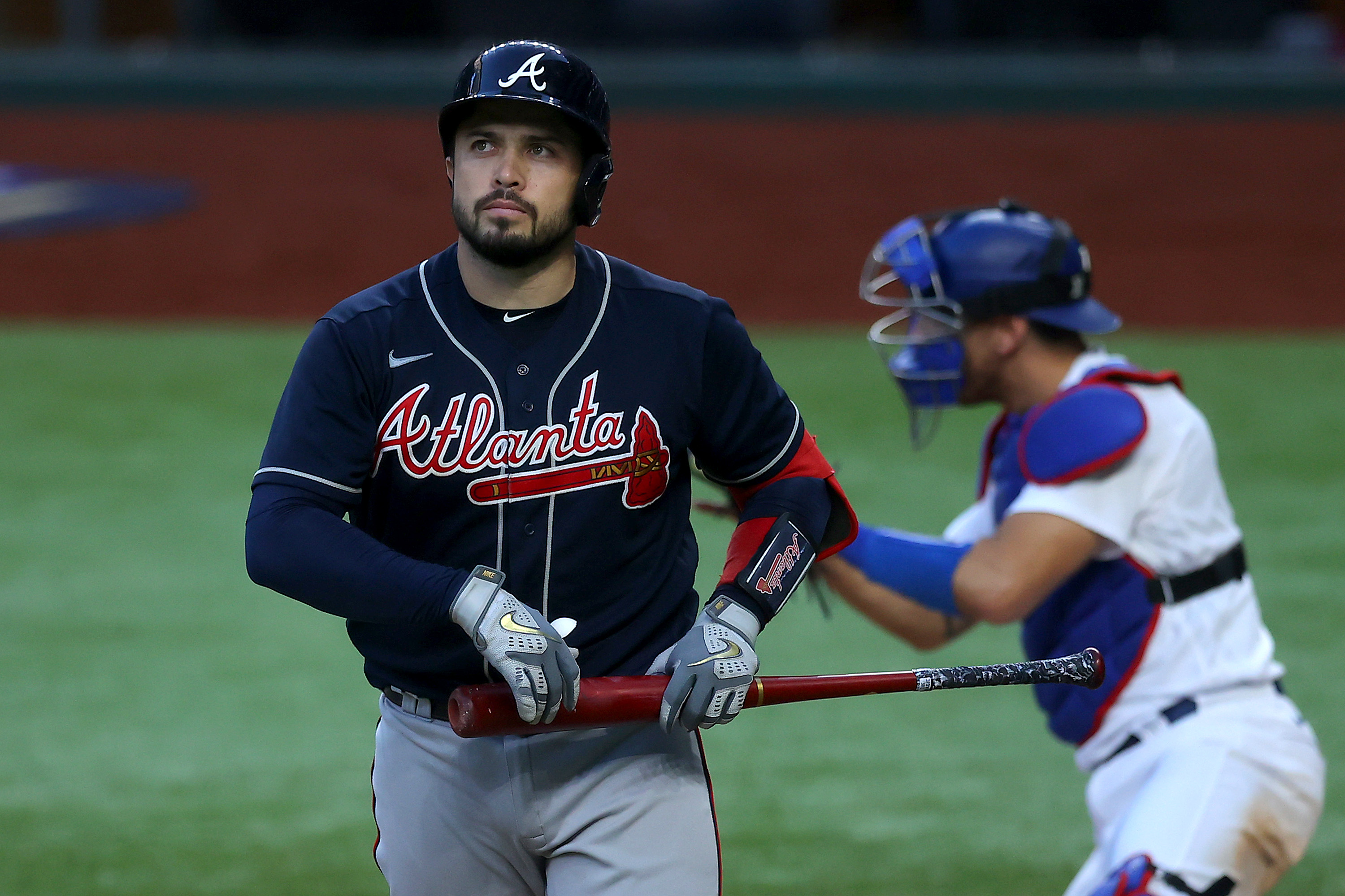 Travis d'Arnaud #16 of the Atlanta Braves reacts after striking out against the Los Angeles Dodgers during the eighth inning in Game Six of the National League Championship Series at Globe Life Field on October 17, 2020 in Arlington, Texas.