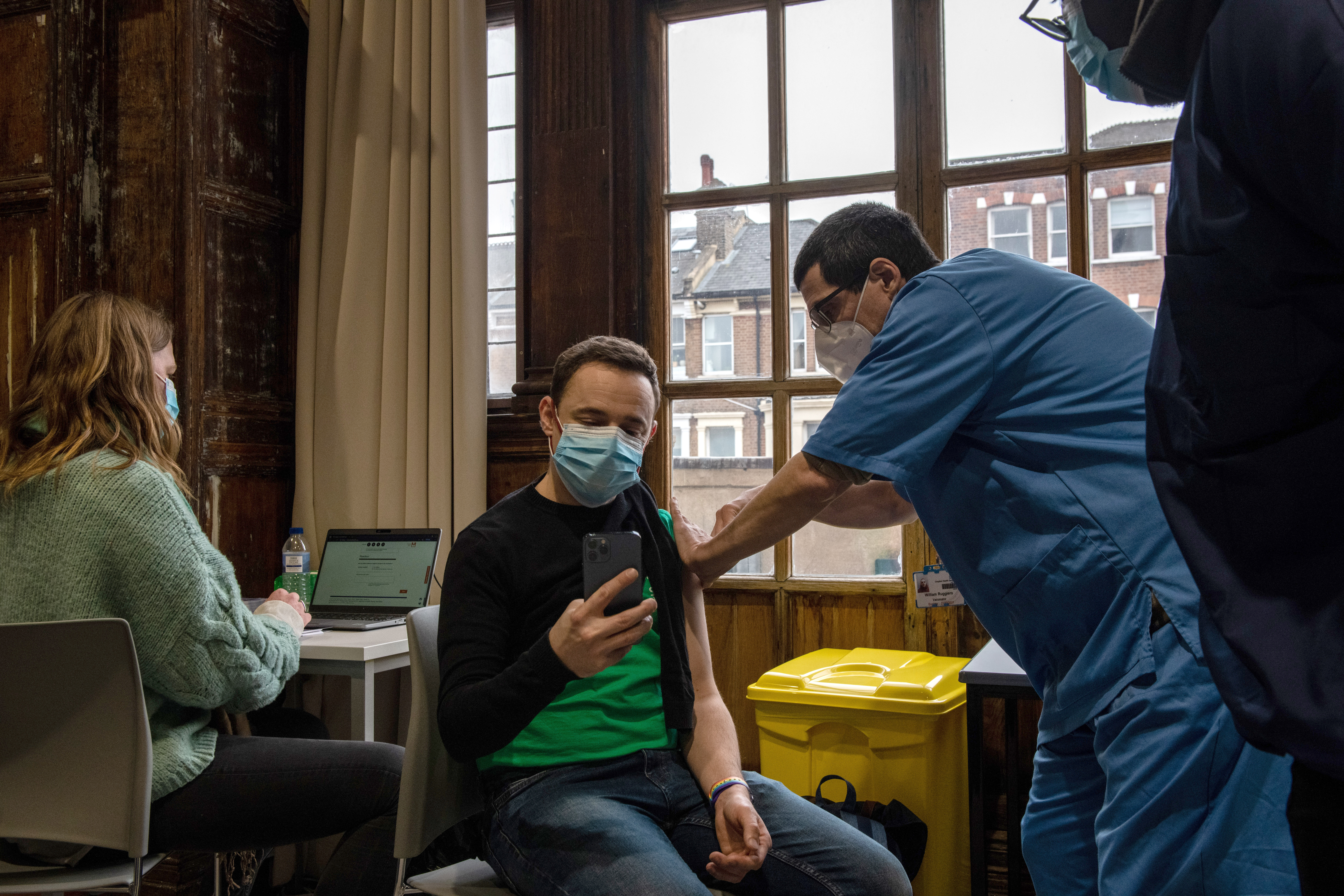 A person sits in a chair while receiving a Covid-19 vaccine from a health care worker.