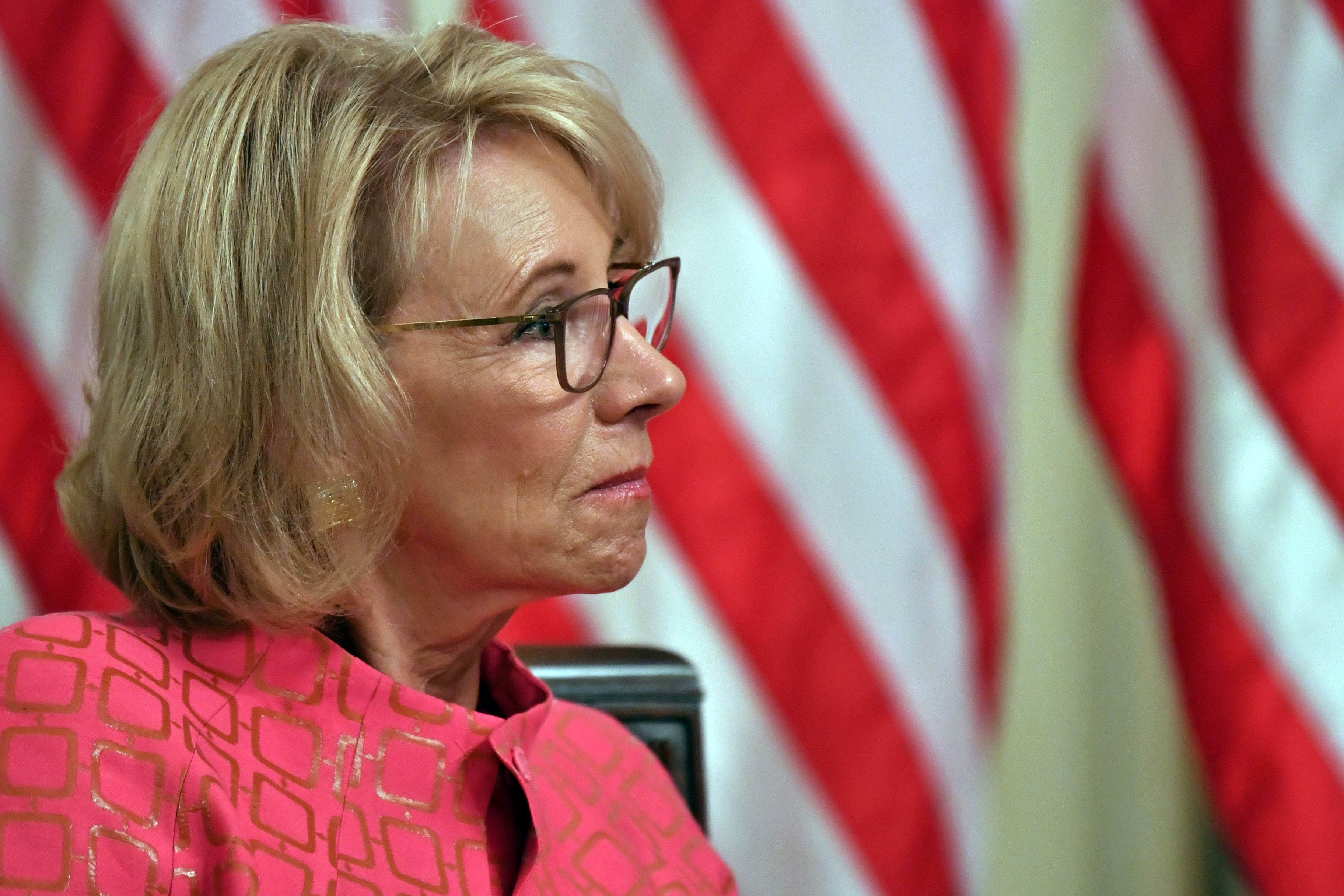 Betsy DeVos, in profile, in front of an American flag.