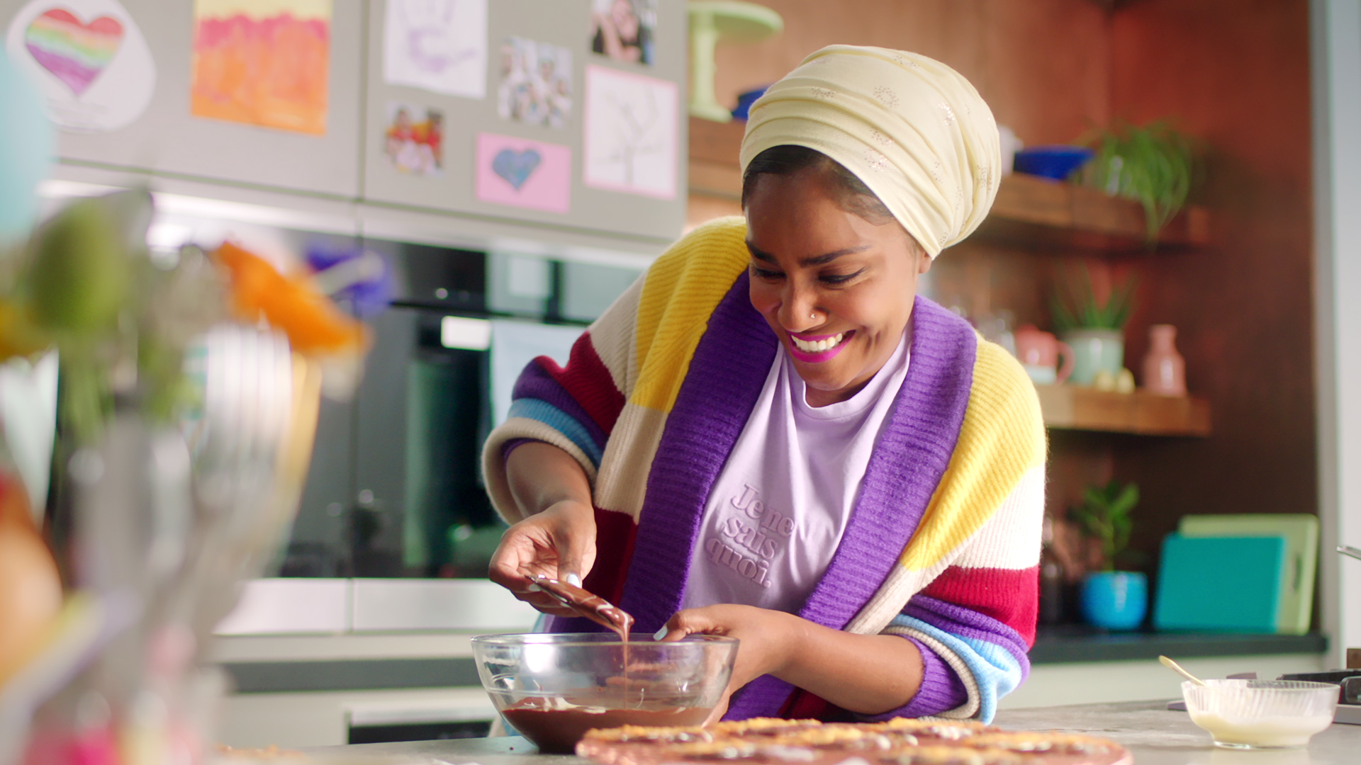 Beaming woman stirring a bowl of chocolate.