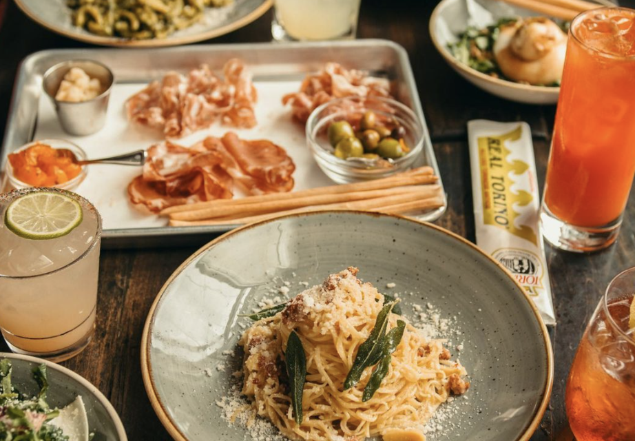 A selection of charcuterie next to a plate of pasta topped with cheese and sage, as well as several colorful cocktails