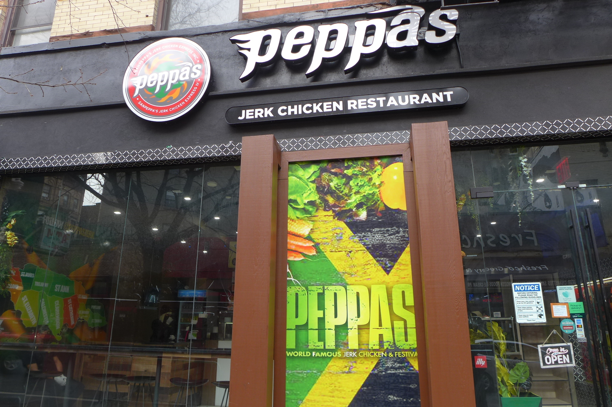 A gleaming storefront with Peppas in lower case, in the colors of black, yellow, and green.