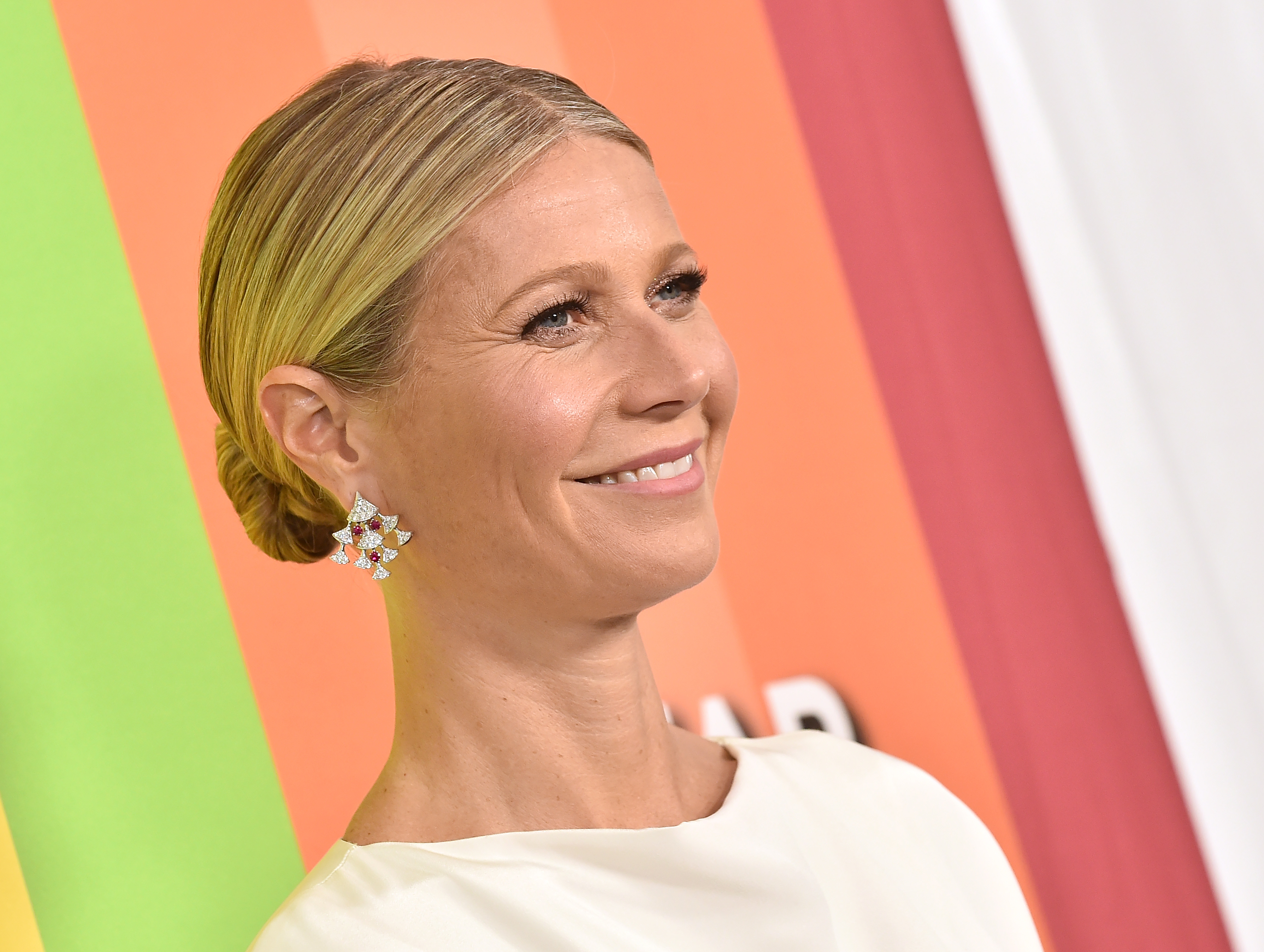 Gwyneth Paltrow smiling in front of a backdrop.