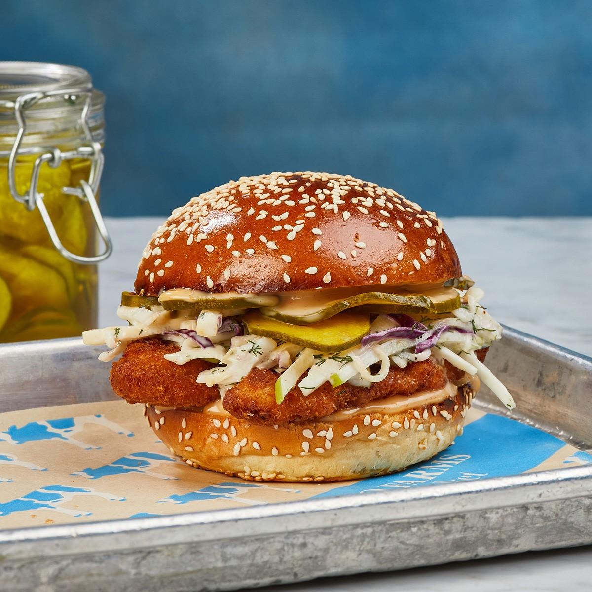 a crispy chicken sandwich with slaw and pickles on a pretzel bun