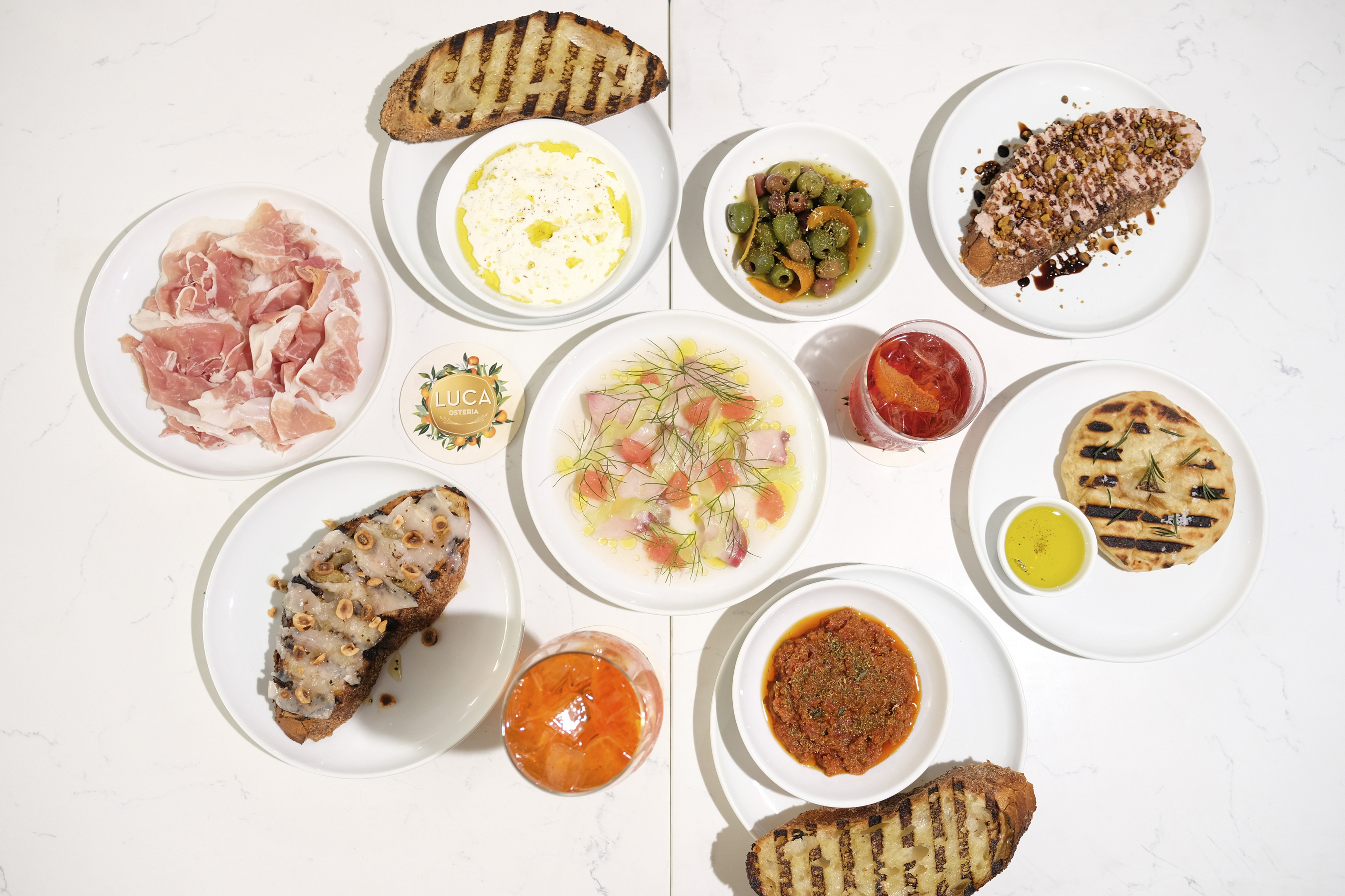 White plates on a white background with featuring lots of sliced meats, oranges, sauces, and grilled breads.