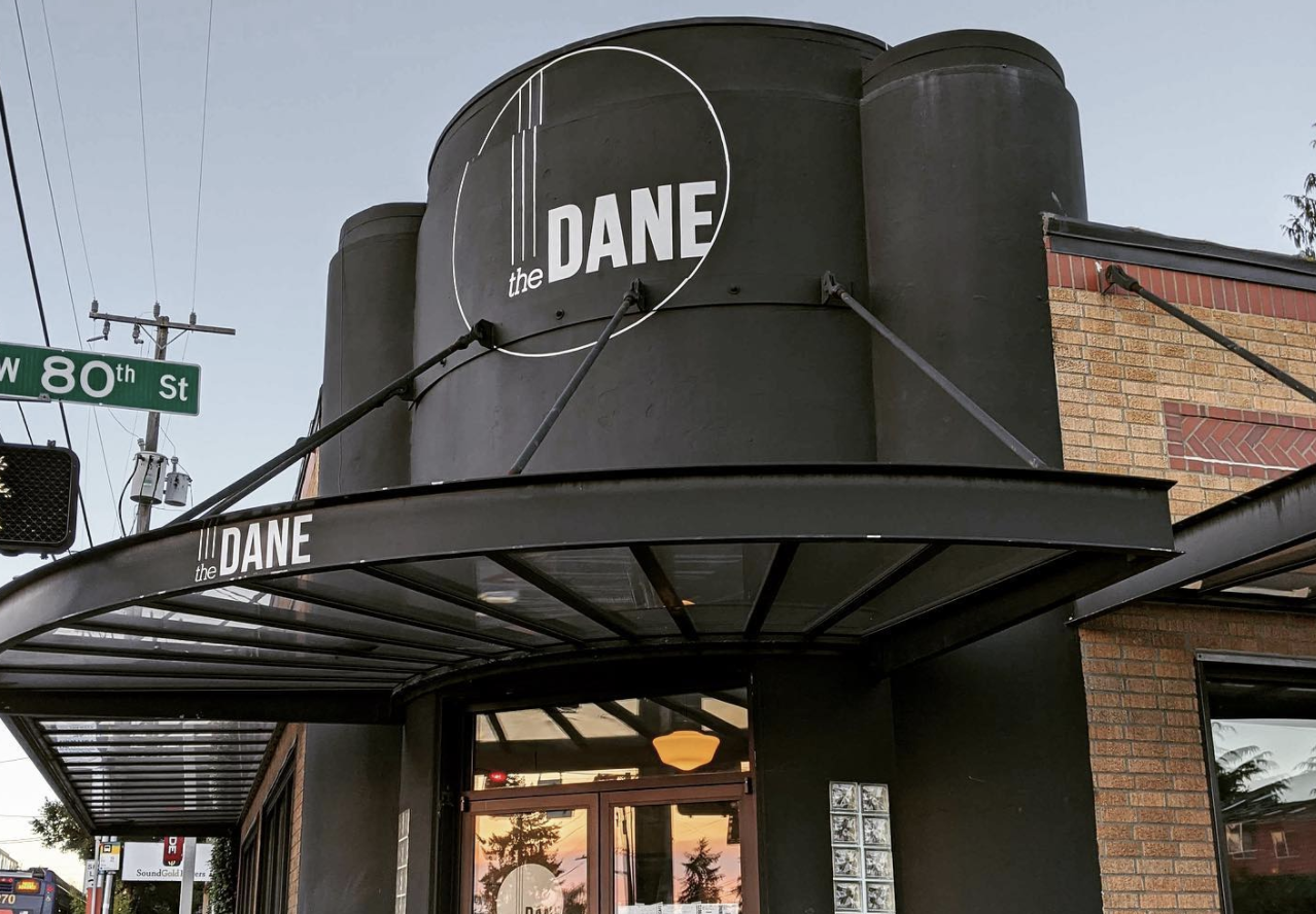 The storefront of Seattle cafe-bar The Dane, with a black storefront and an art deco logo