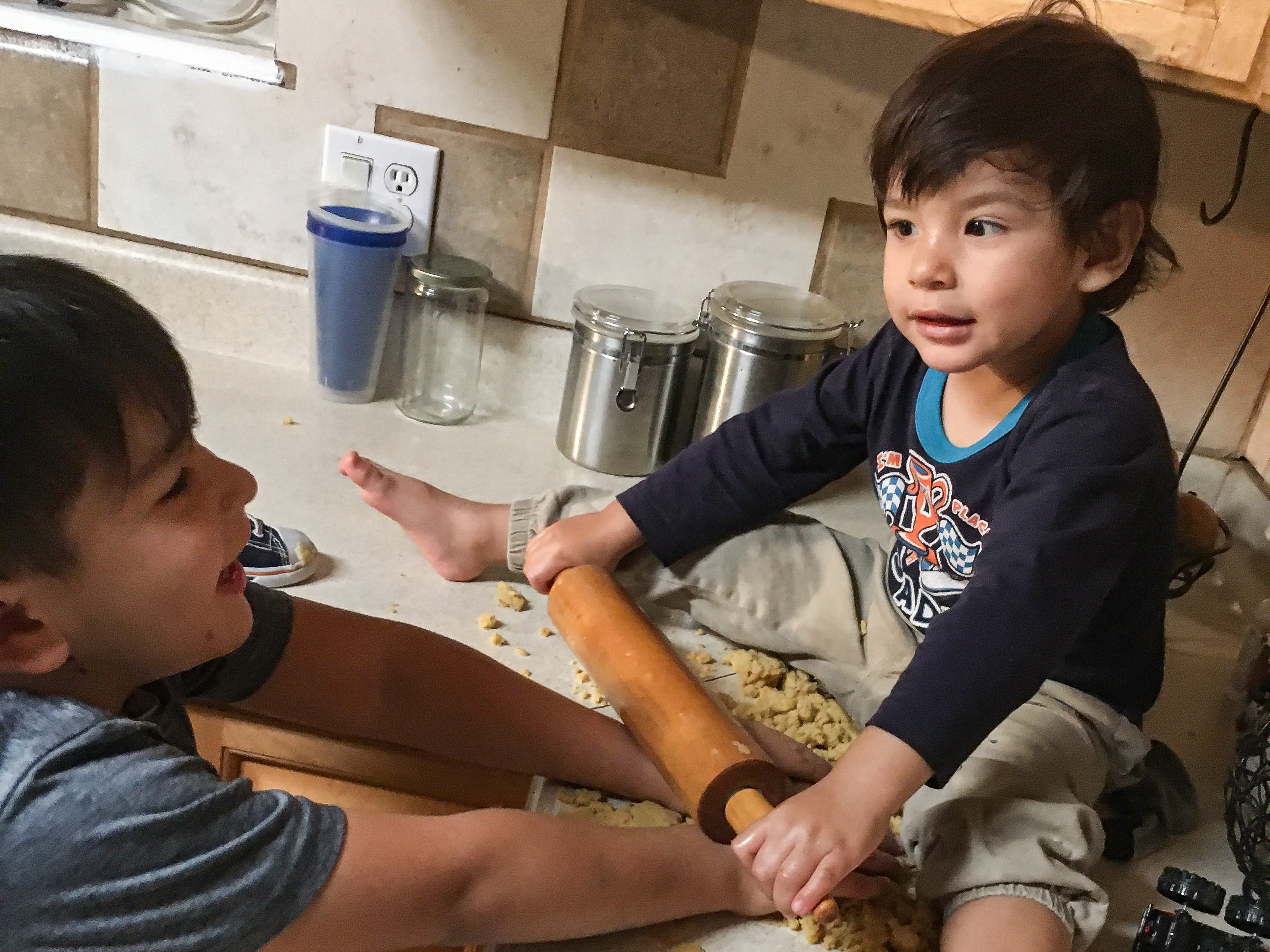 A 2-year-old sits on the counter holding a rolling pin while his 5-year-old brother helps him roll out buñuelos at home.