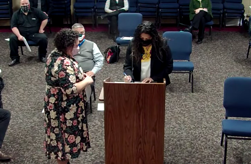 Janet Estrada signs paperwork at the podium as she is sworn in.