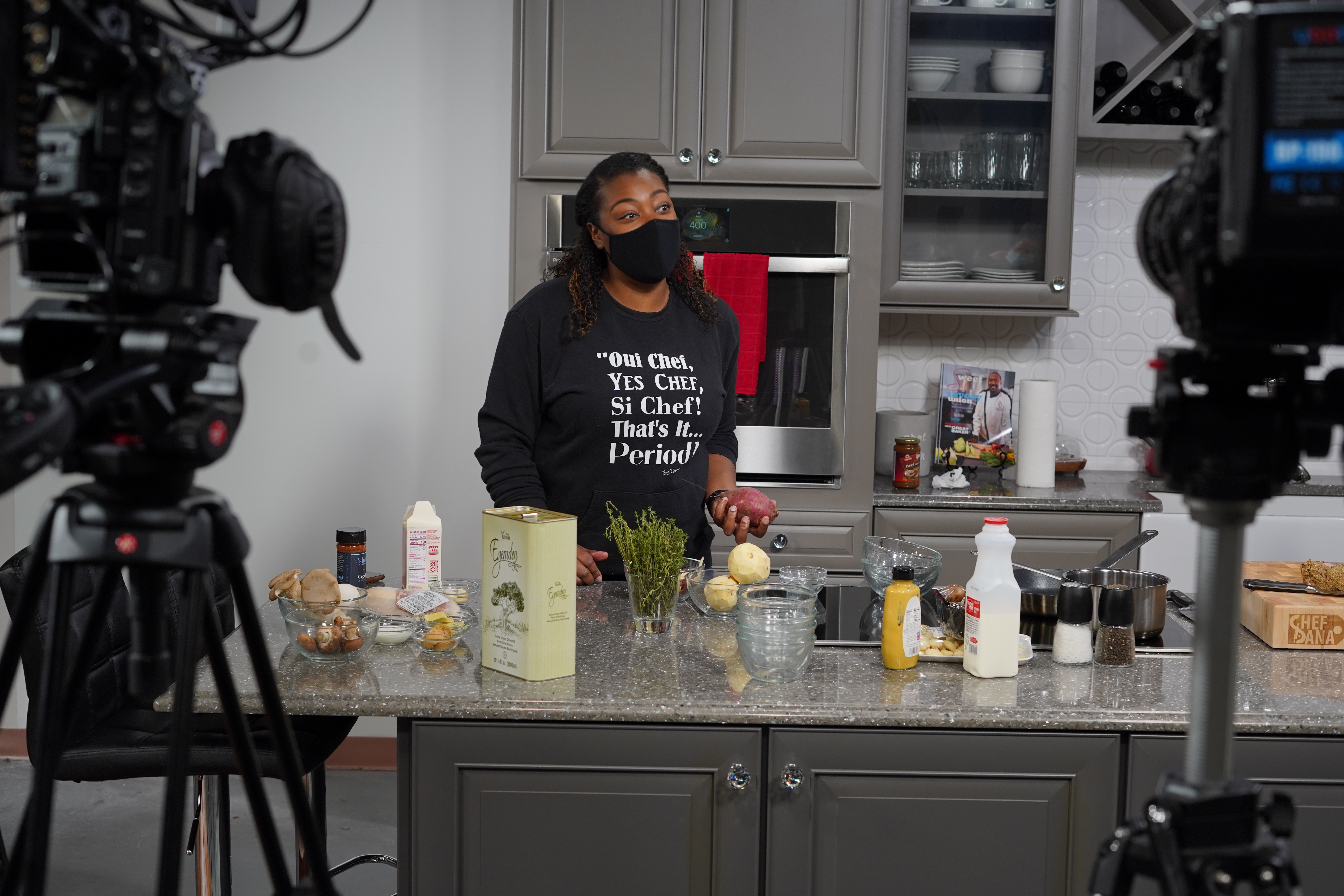 A Black woman wearing a black shirt and black face mask holds a potato while standing in a kitchen. Ingredients like olive oil are scattered on the counter, and a pair of cameras sits in the background.