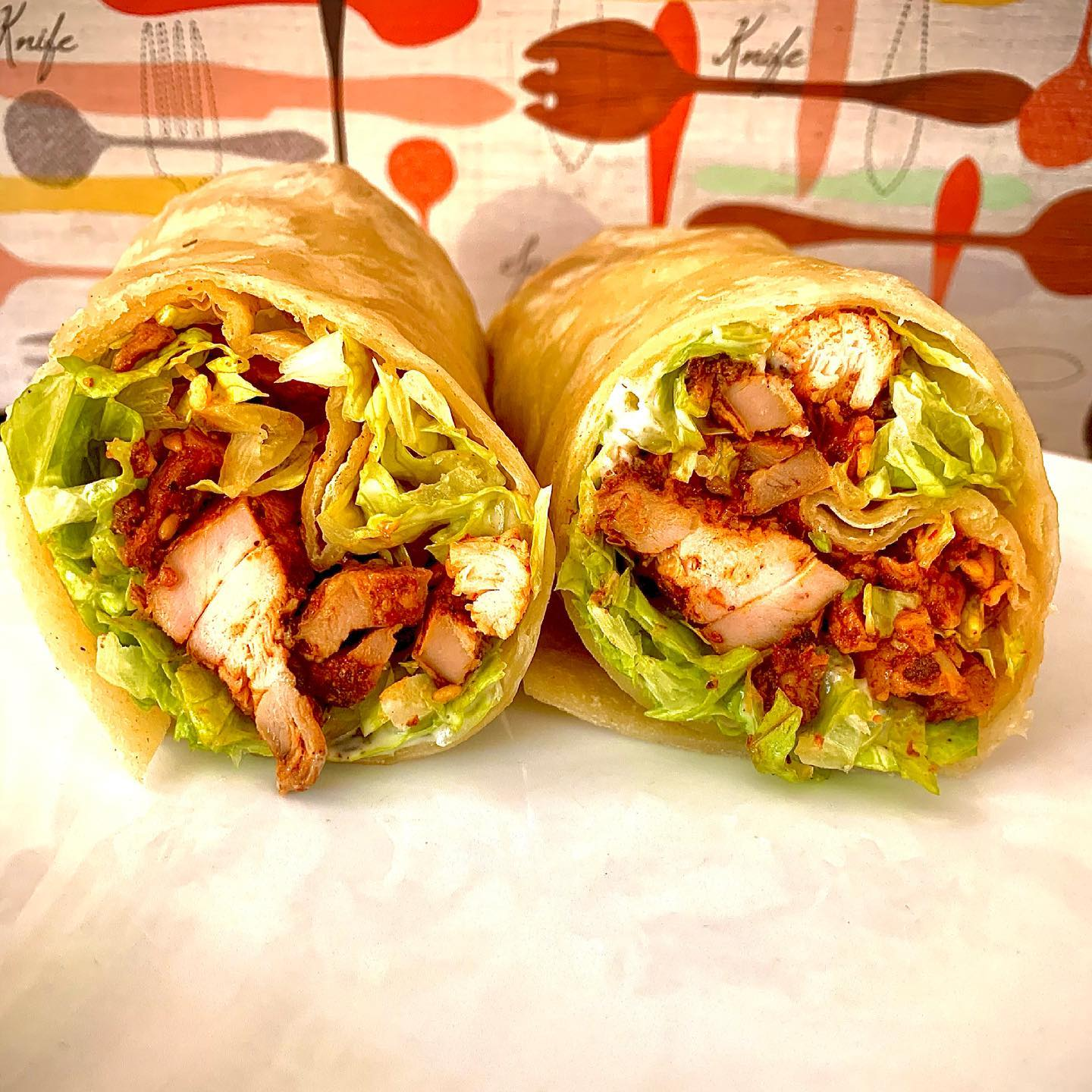 An Al pastor chicken burrito cut in half with lettuce, cheese, and chunks of roasted chicken