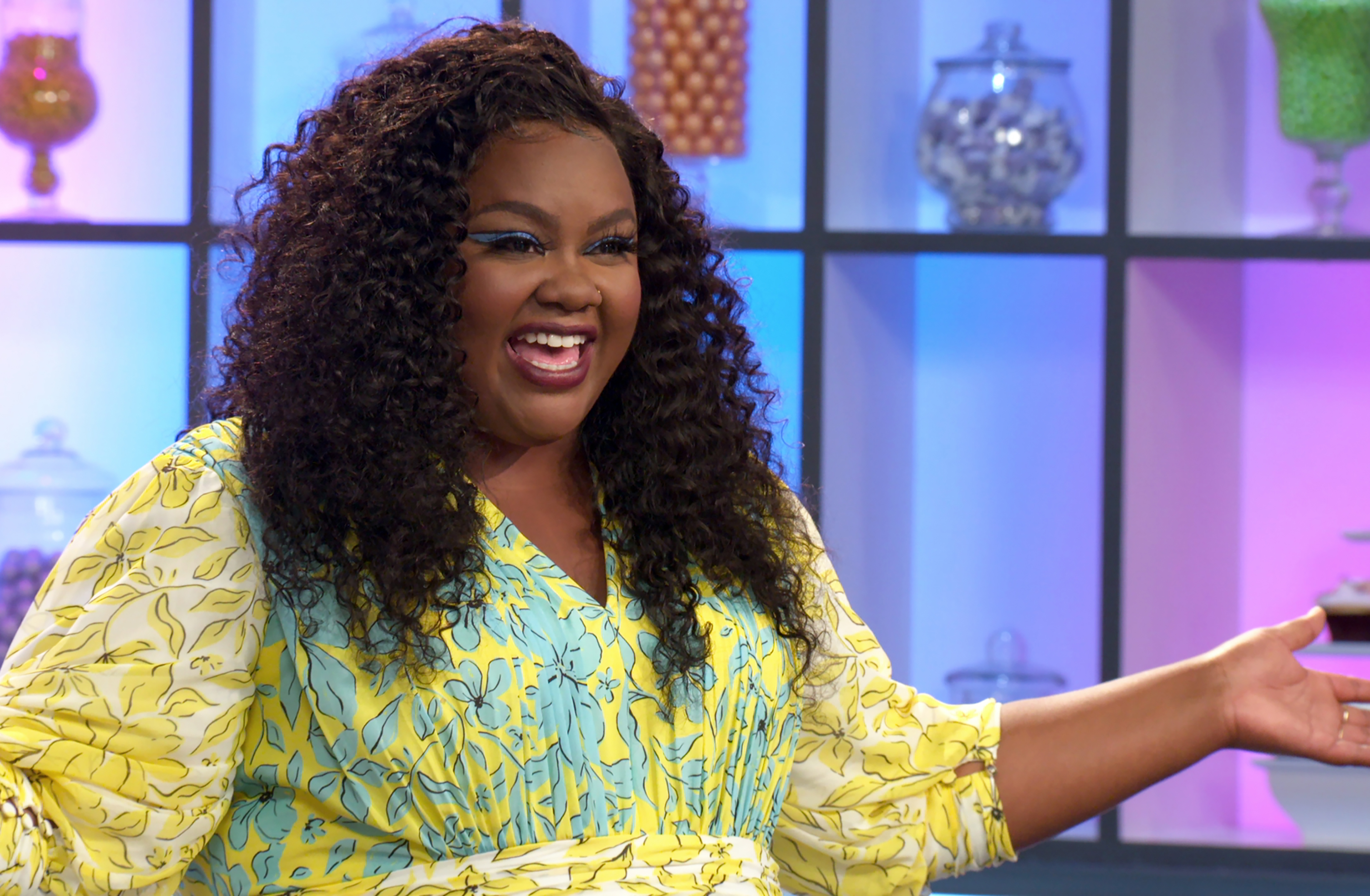 Nicole Byer stands in front of a multi-colored screen wearing a floral yellow and blue dress
