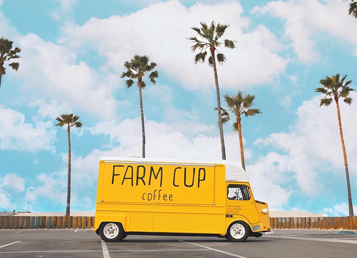 Farm Cup Coffee's bright yellow van will park permanently at a new West Hollywood space, here backgrounded by palm trees and blue sky.