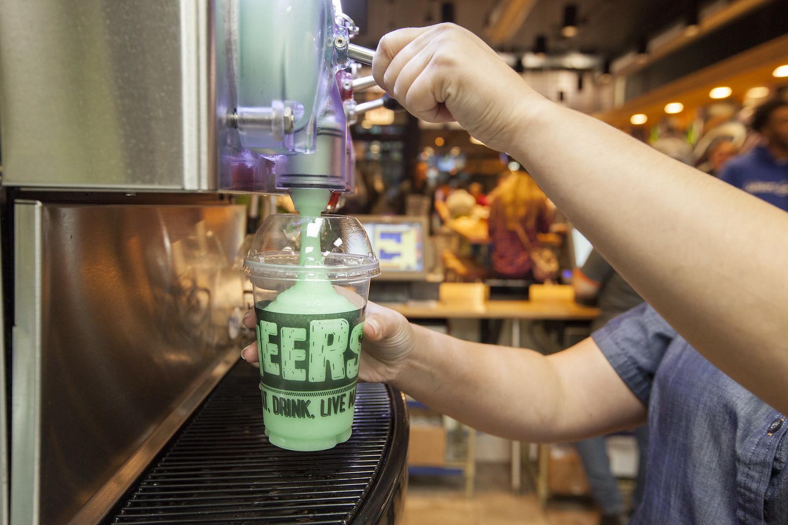 A slushie machine pouring a green slushie into a plastic cup.