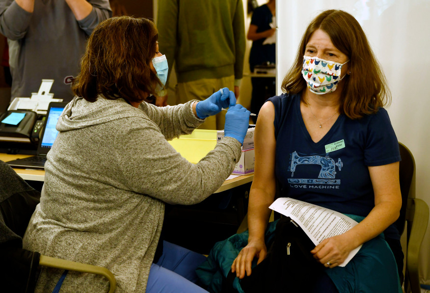 A medical worker administers a COVID-19 vaccine in the right arm of a school nurse as she sits.