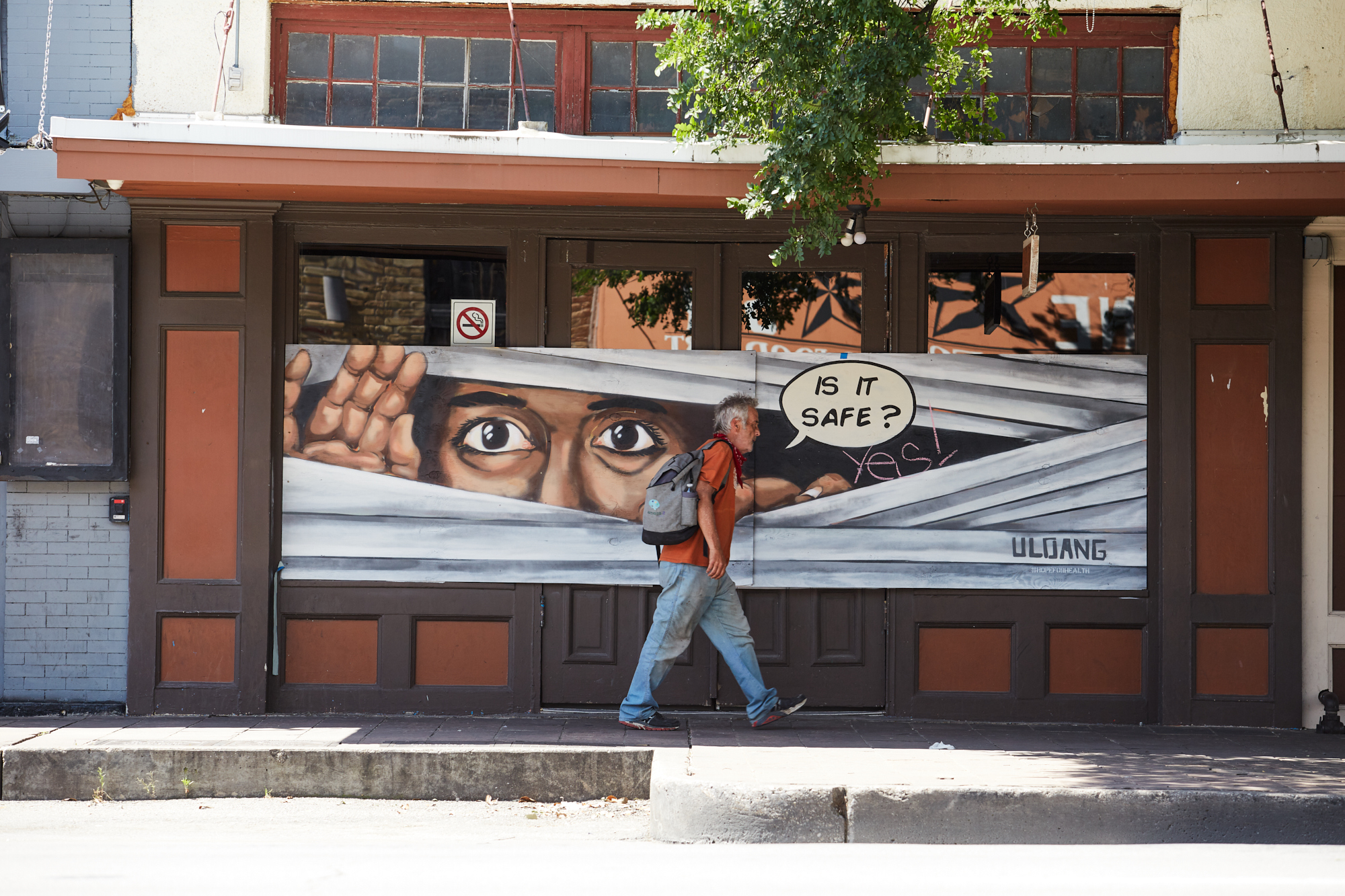 A man walking in front of a temporarily shuttered bar on East Sixth Street back in early May 2020