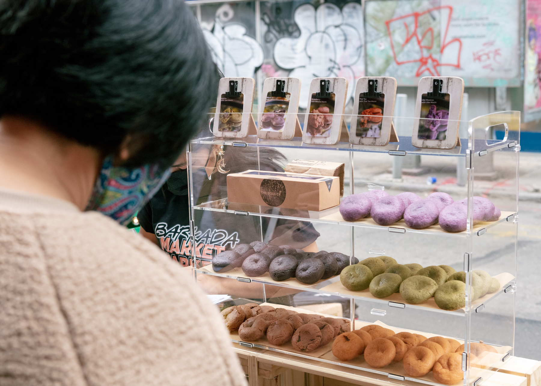 Multi-colored cookies placed in a display cake and a woman is looking at them