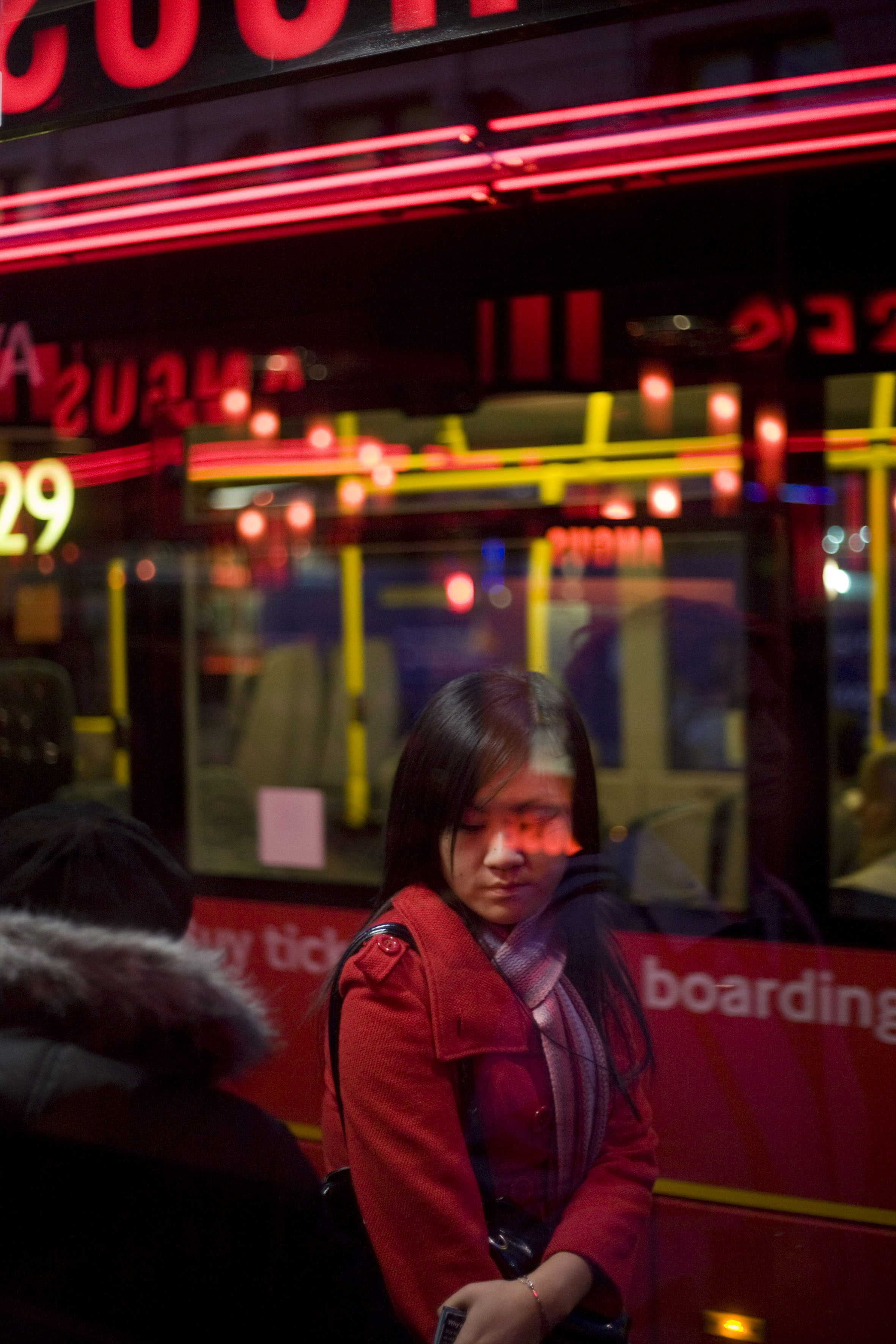 A young commuter woman awaits her bus on a southbound route at a stop on Charing Cross Road in central London. Surrounded by red hues from the bus behind the girl and from lettering from an Angus Steakhouse restaurant,