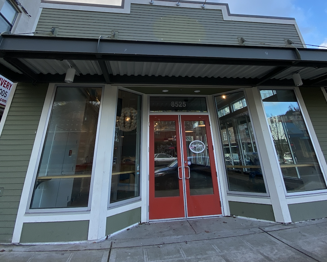 A dark green storefront of a coffeeshop with a red door and a small awning