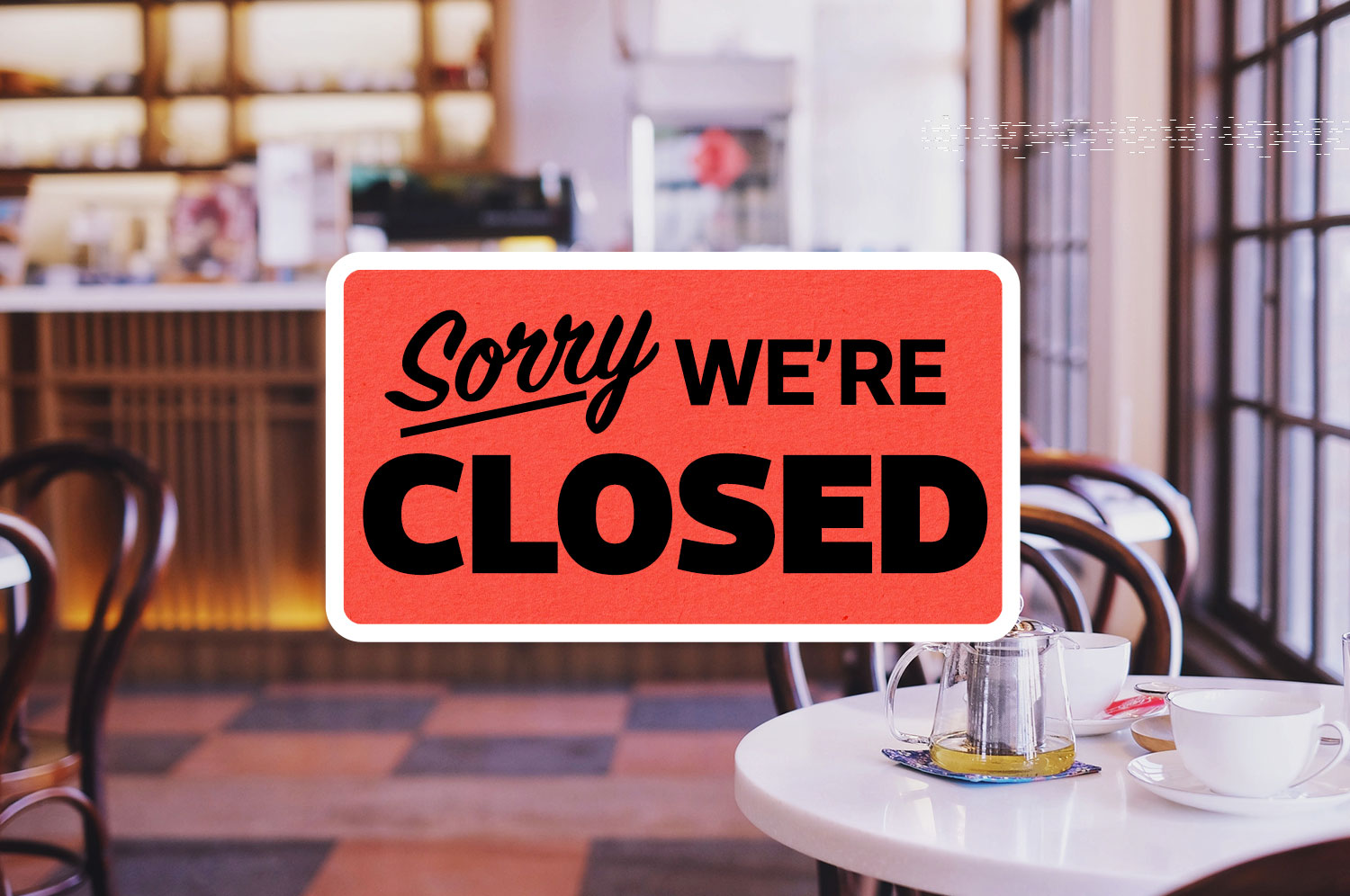 """A casual cafe with a red sign overlaying the image that reads """"Sorry We're Closed"""""""