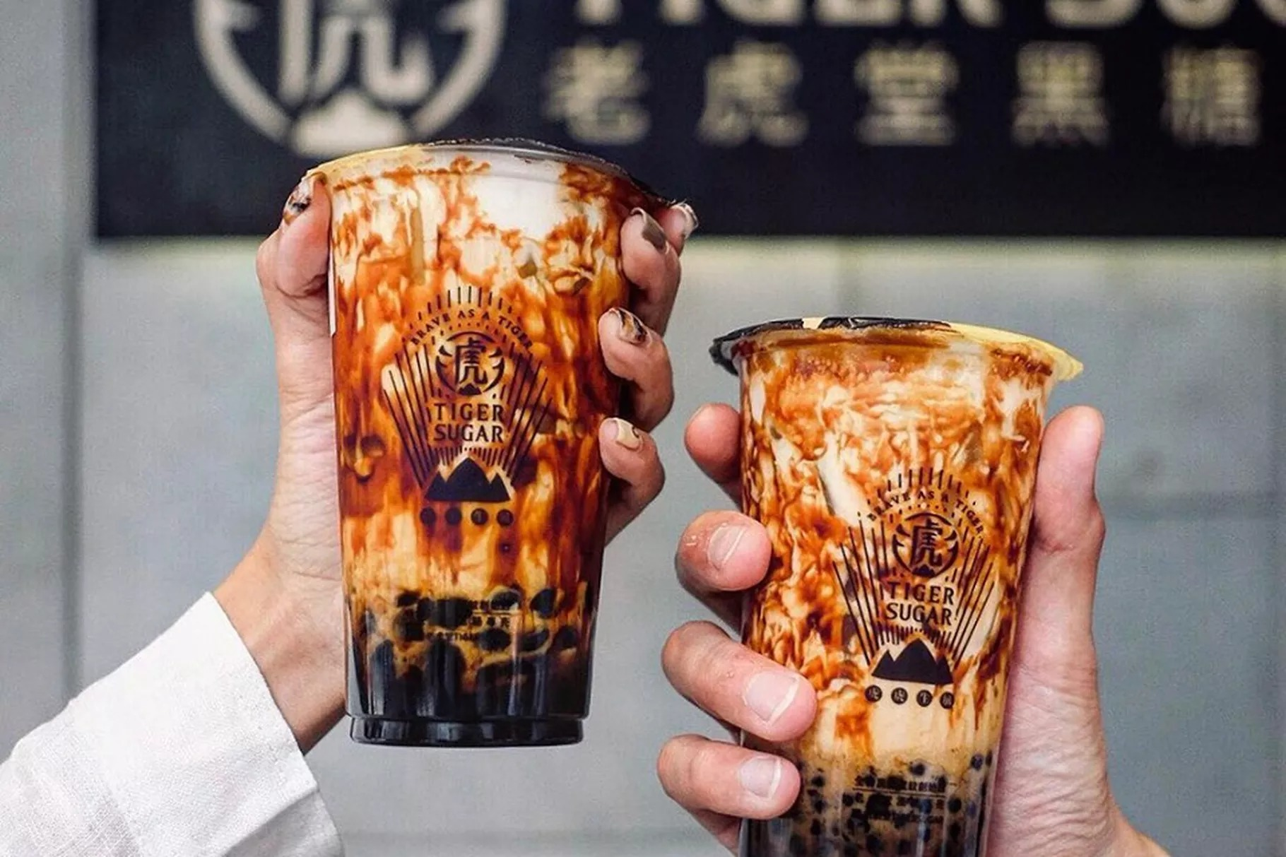 Two hands hold cups of brown sugar boba from Taiwanese chain Tiger Sugar. The iced tea drink is milky white with streaks of dark brown.