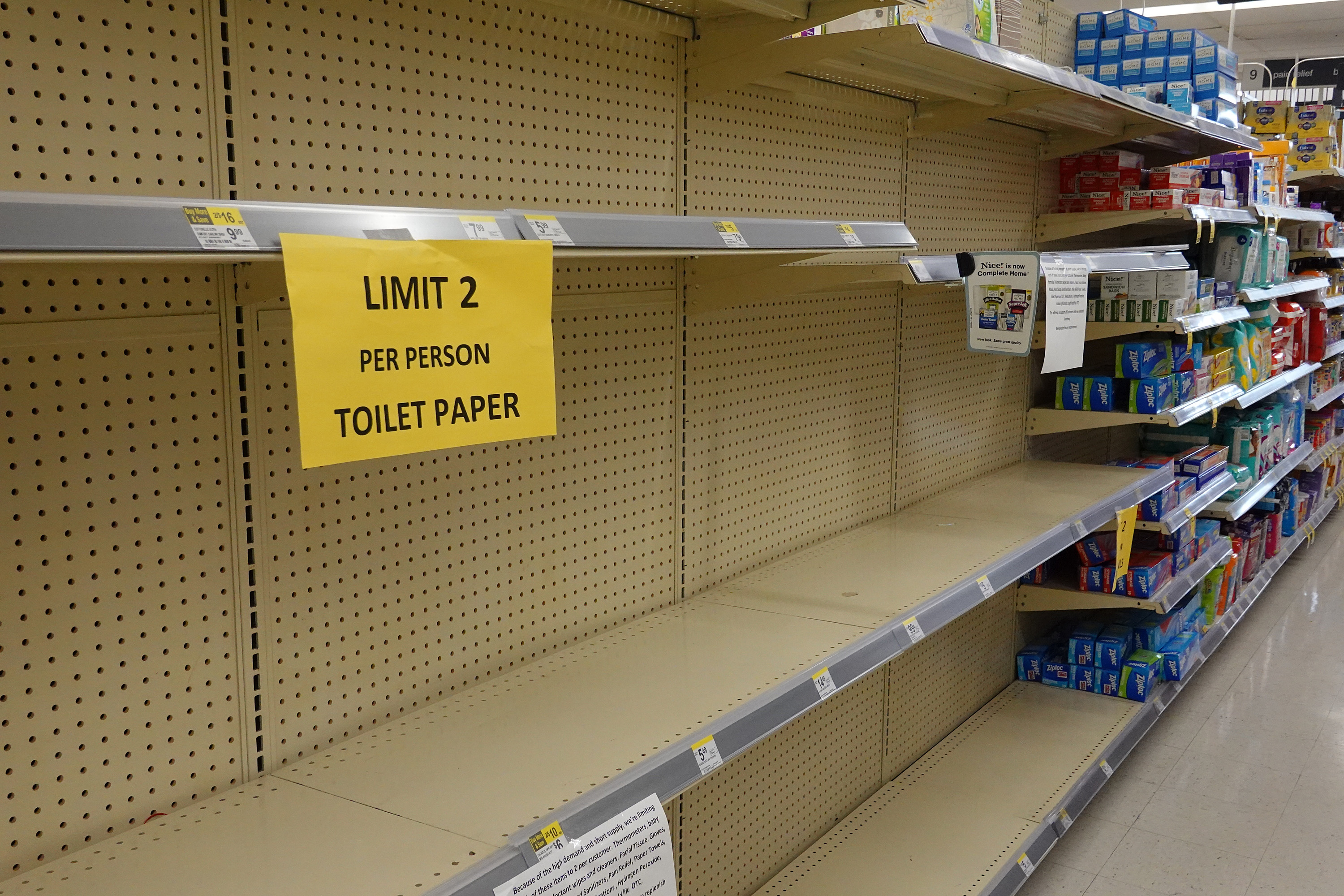 """Empty toilet paper shelves in a store, with a """"limit 2 per person"""" sign."""