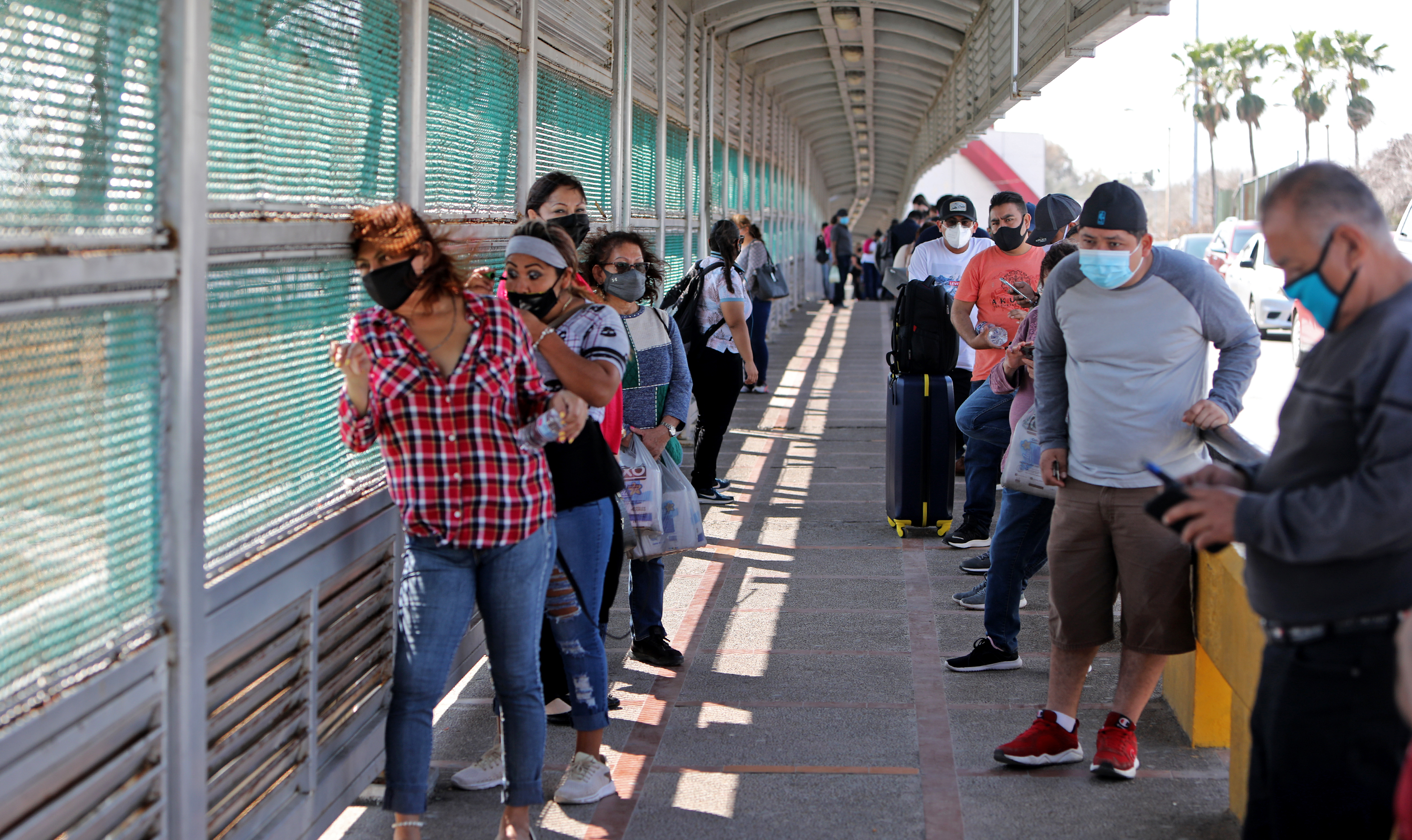 Pedestrians wait in line to cross the Gateway International Bridge from Matamoros, Tamaulipas, Mexico, to Brownsville, Texas, Wednesday, Feb. 24, 2021.