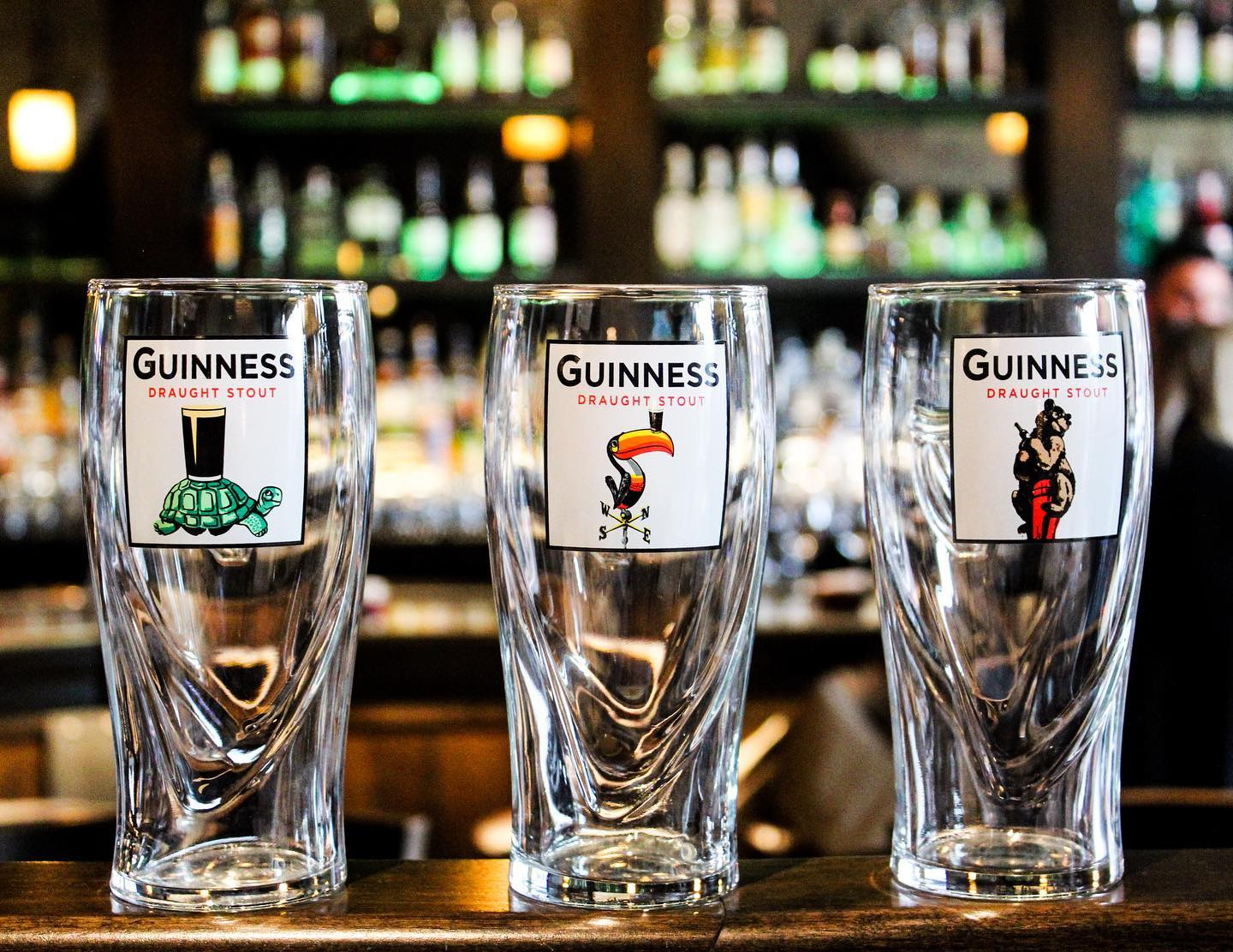 Three empty pint glasses with Guinness logos.