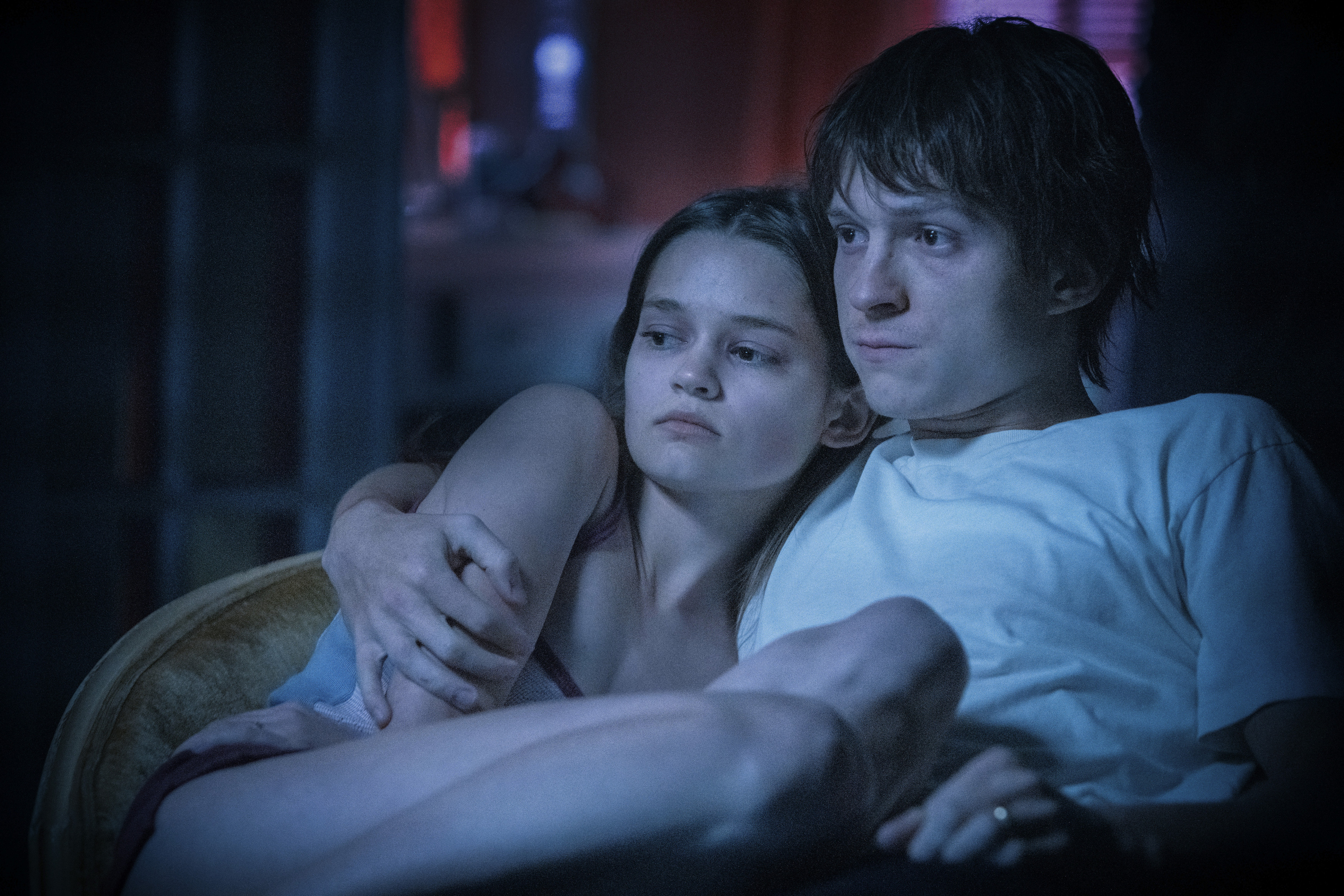 Cherry (Tom Holland) and his wife Emily (Ciara Bravo), bathed in blue light, sit strung out on the couch after shooting up heroin