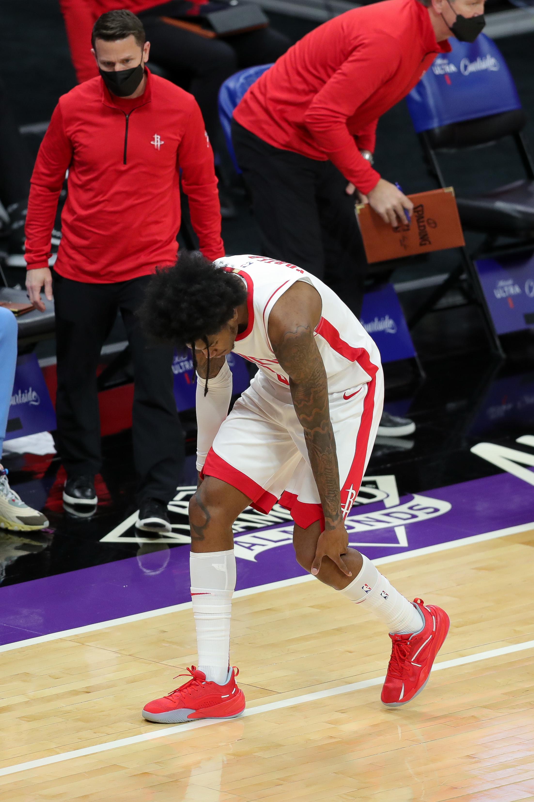 Houston Rockets guard Kevin Porter Jr. holds his left knee during the second quarter against the Sacramento Kings at Golden 1 Center.