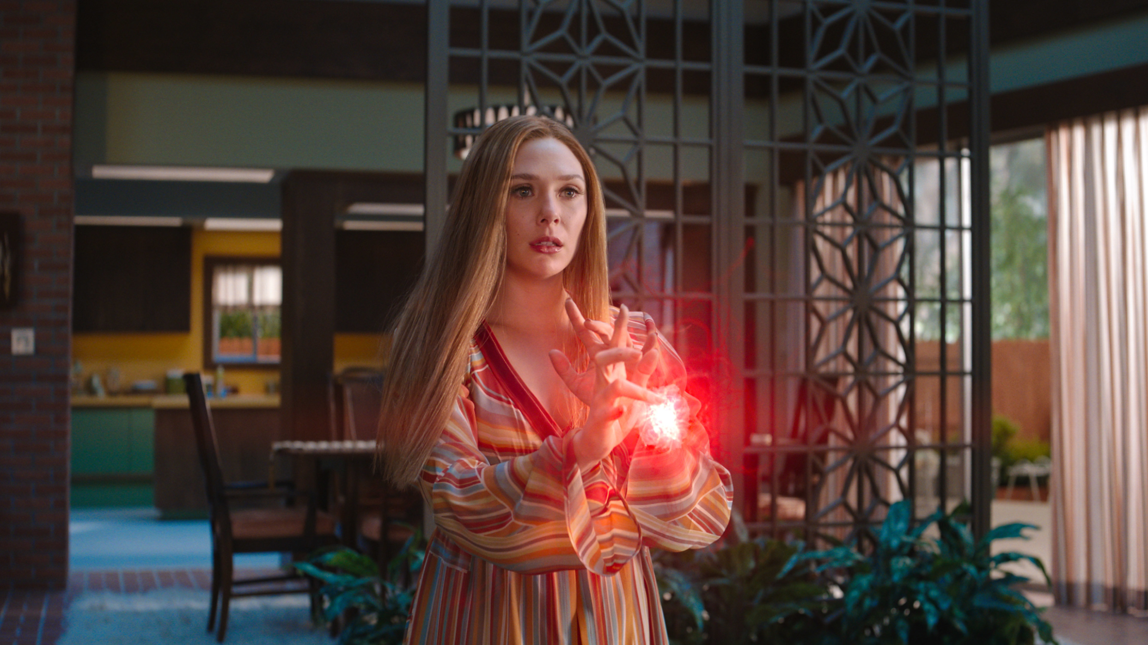 A red ball of energy glows in Wanda's hands as she prepares to do some magic.