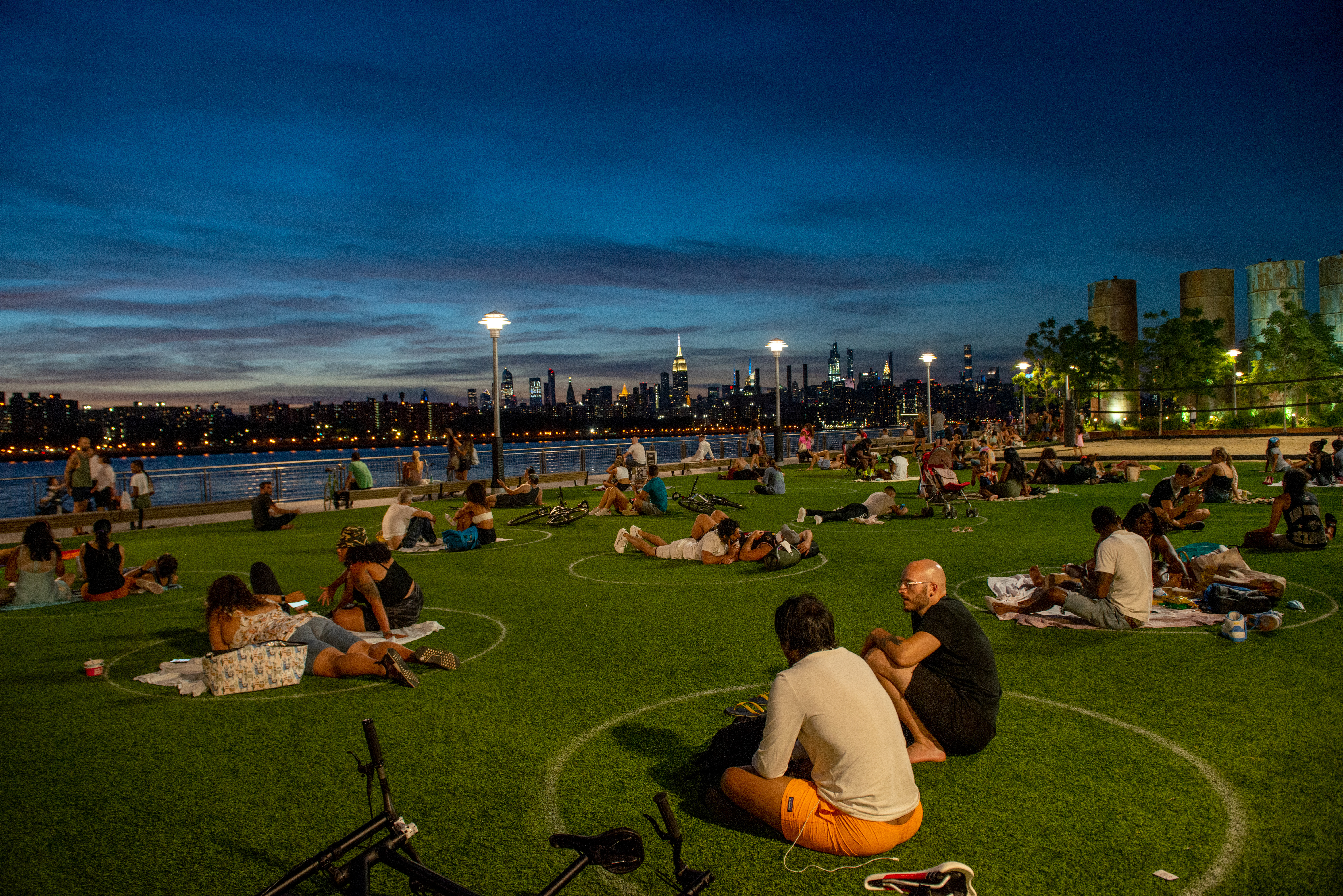 People sit in prescribed circles at a New York City park.