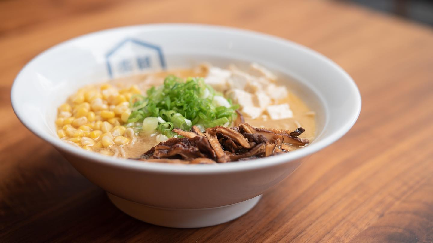 A white bowl of ramen garnished with tofu, green onions, corn, and sliced mushrooms. The bowl is on a wood table.