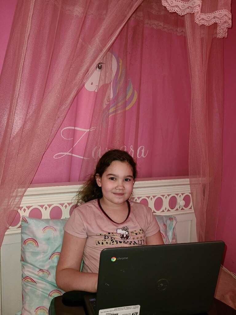 Chicago student Zamara sits with her laptop on her bed, she has pink curtains and a blue bedspread.
