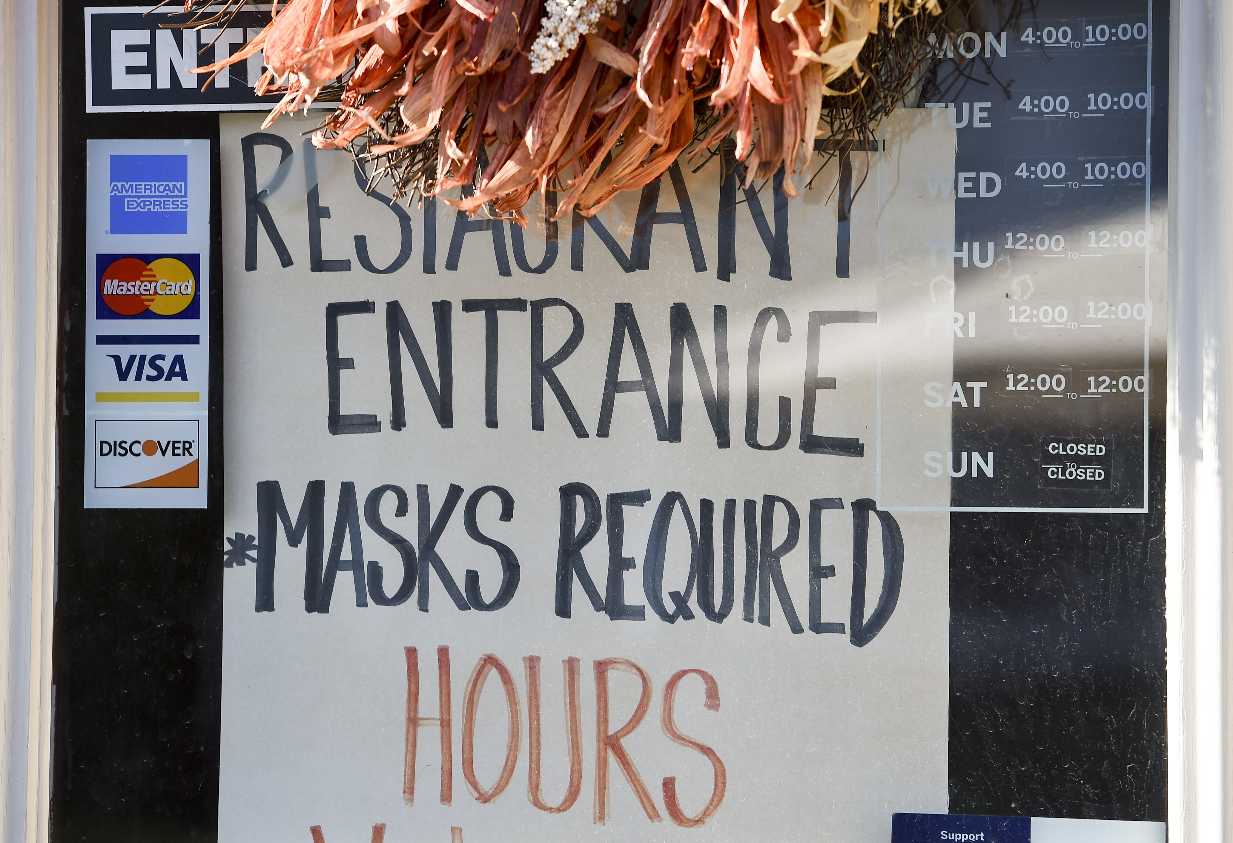 a sign on a door that says restaurant entrance masks required and hours