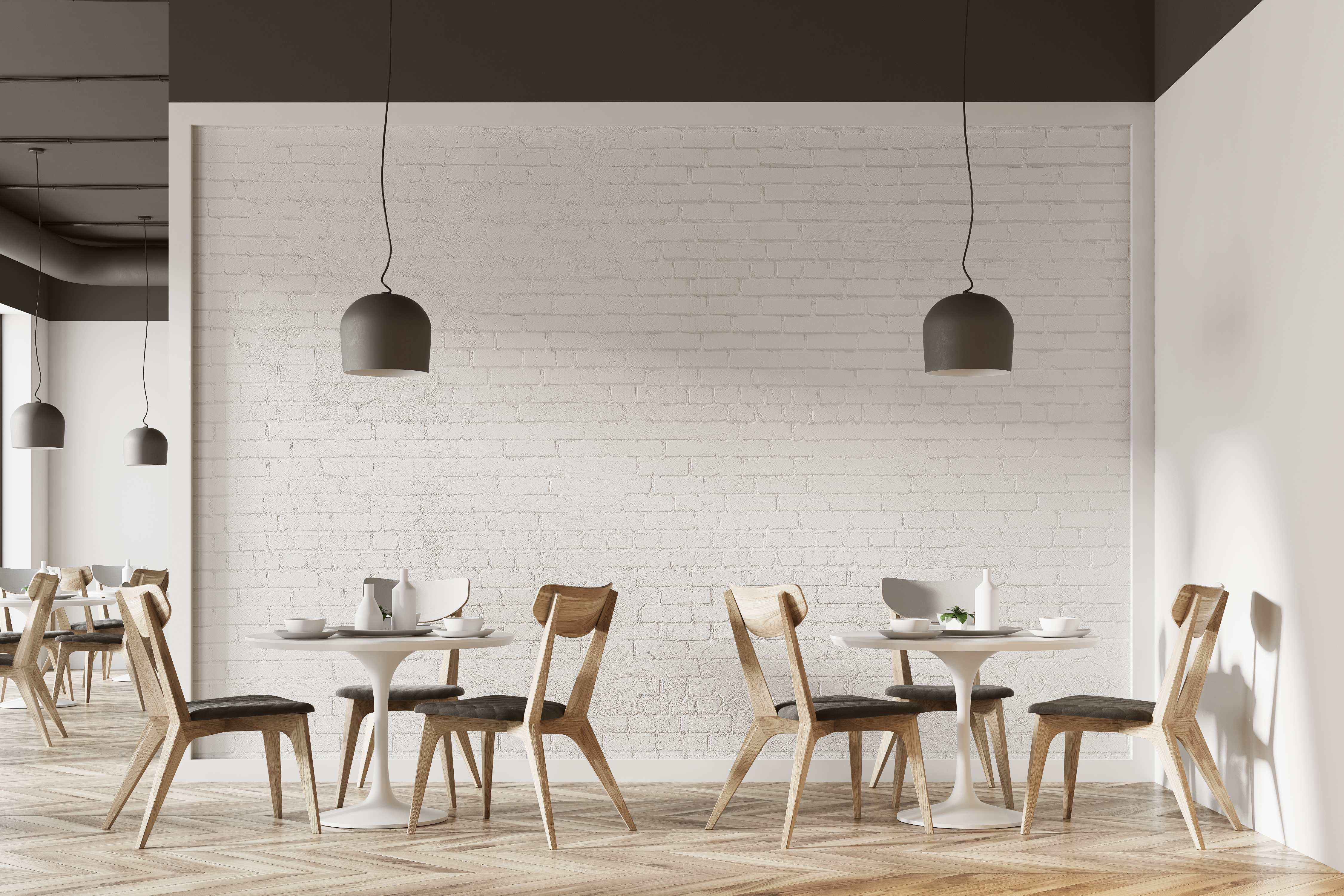 Empty tables at a cafe with a modern, minimalist design and big hanging light fixtures.
